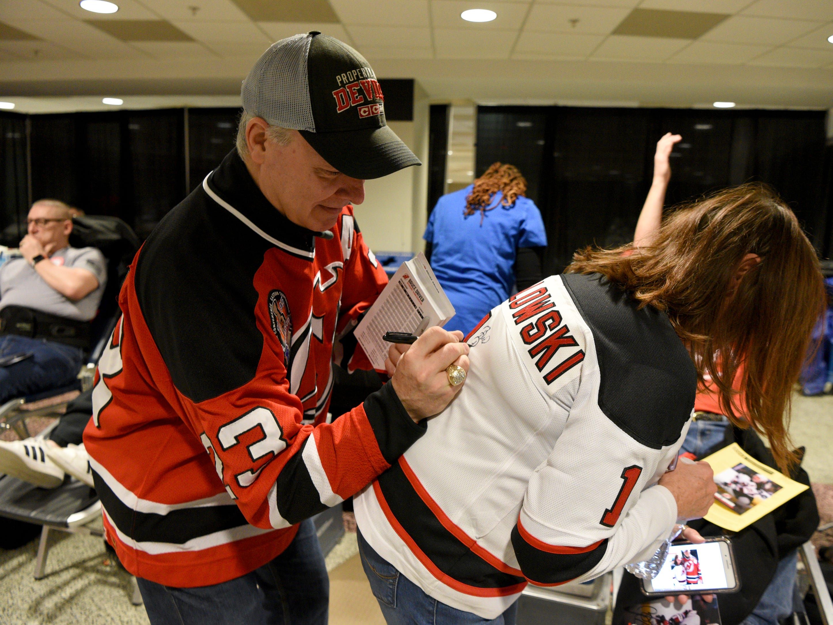 The New Jersey Devils and RWJBarnabas Health hosted their third annual blood drive in coordination with the American Red Cross on Sunday, March 10, 2019 at the Prudential Center in Newark.  Devils' alumni Bruce Driver, a member of the 1995 Devils Stanley Cup winning team, autographs a jersey for Linda Michalowski of Florham Park.