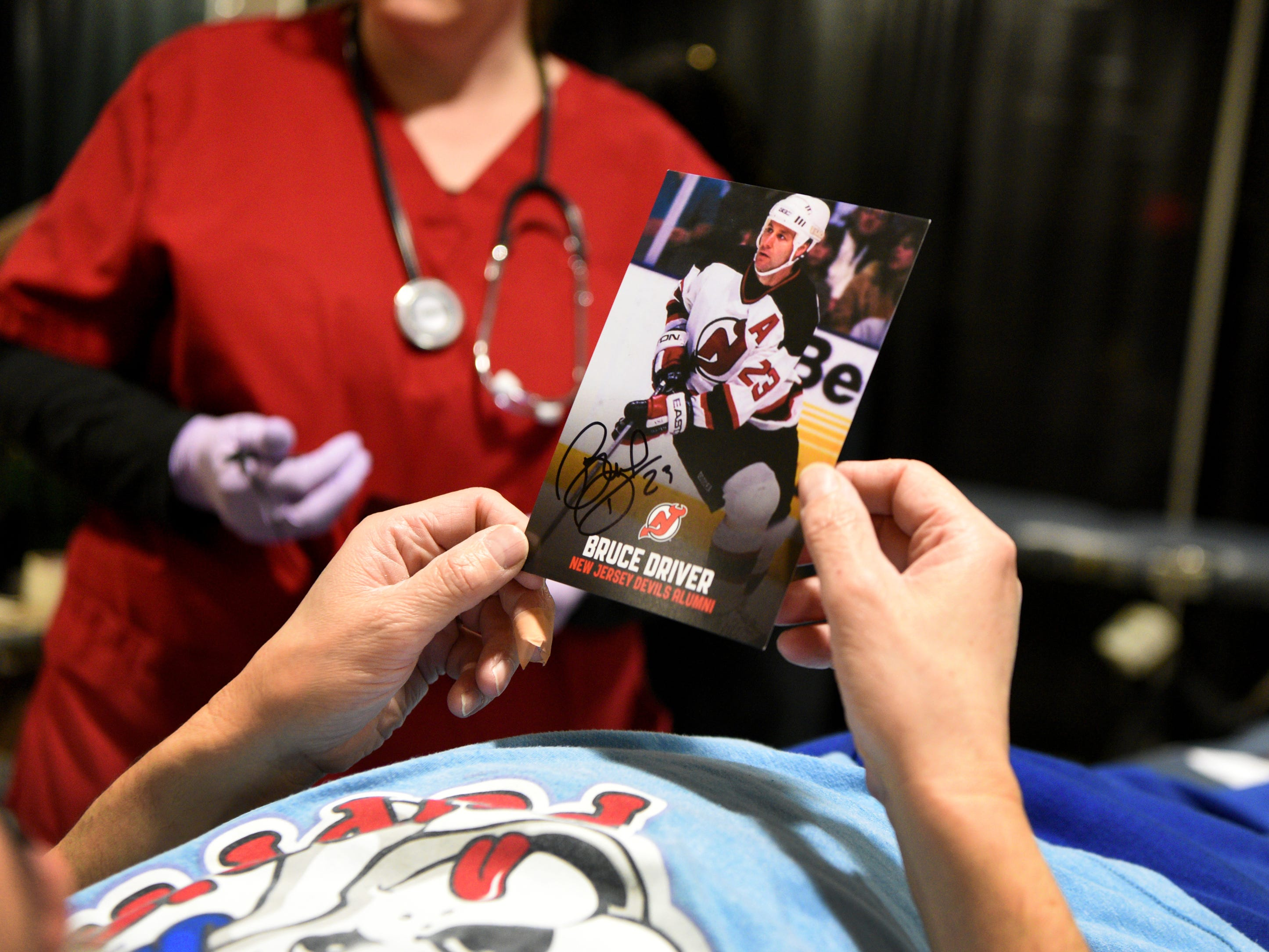 The New Jersey Devils and RWJBarnabas Health hosted their third annual blood drive in coordination with the American Red Cross on Sunday, March 10, 2019 at the Prudential Center in Newark. A blood holds a card autographed by  Devils' alumni Bruce Driver, a member of the 1995 Devils Stanley Cup winning team.