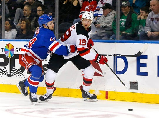 Mar 9, 2019; New York, NY, USA;  New Jersey Devils center Travis Zajac (19) plays the puck against New York Rangers defenseman Neal Pionk (44) during the first period at Madison Square Garden.