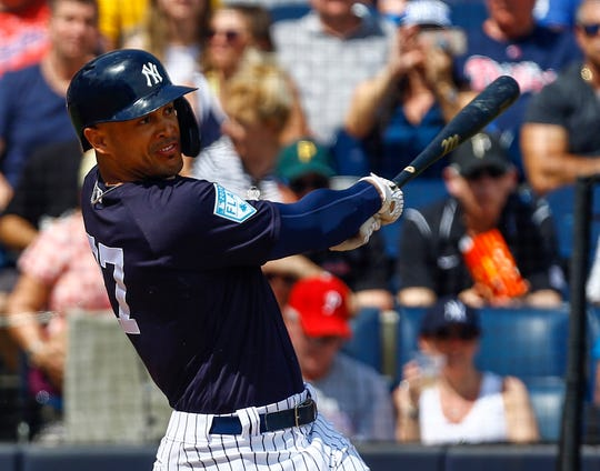 Mar 10, 2019; Tampa, FL, USA; New York Yankees left fielder Giancarlo Stanton (27) hits a single during the first inning against the Pittsburgh Pirates at George M. Steinbrenner Field.
