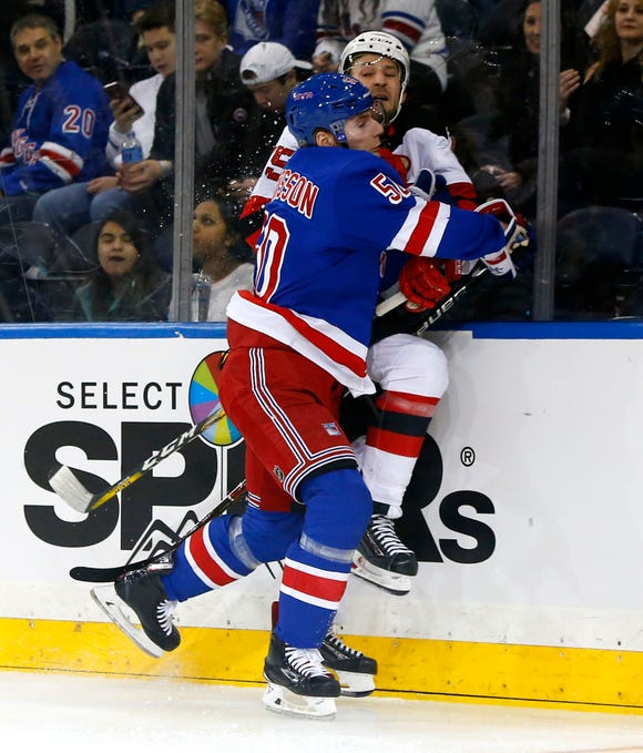 Mar 9, 2019; New York, NY, USA;  New York Rangers center Lias Andersson (50) check New Jersey Devils right wing Nick Lappin (15) during the first period at Madison Square Garden.