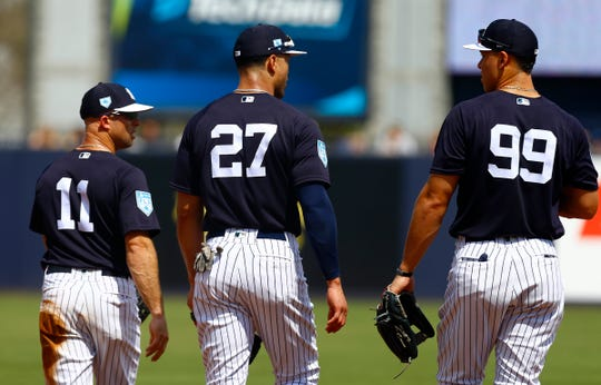 Mar 10, 2019; Tampa, FL, USA; New York Yankees center fielder Brett Gardner (11) and left fielder Giancarlo Stanton (27) and right fielder Aaron Judge (99) walk out to the outfield during the second inning against the Pittsburgh Pirates at George M. Steinbrenner Field.