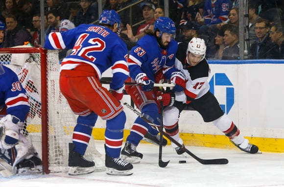 New York Rangers defenseman Brendan Smith (42) and center Mika Zibanejad (93) defend against New Jersey Devils left wing Kenny Agostino (17) during the first period at Madison Square Garden Mar 9, 2019; New York, NY, USA