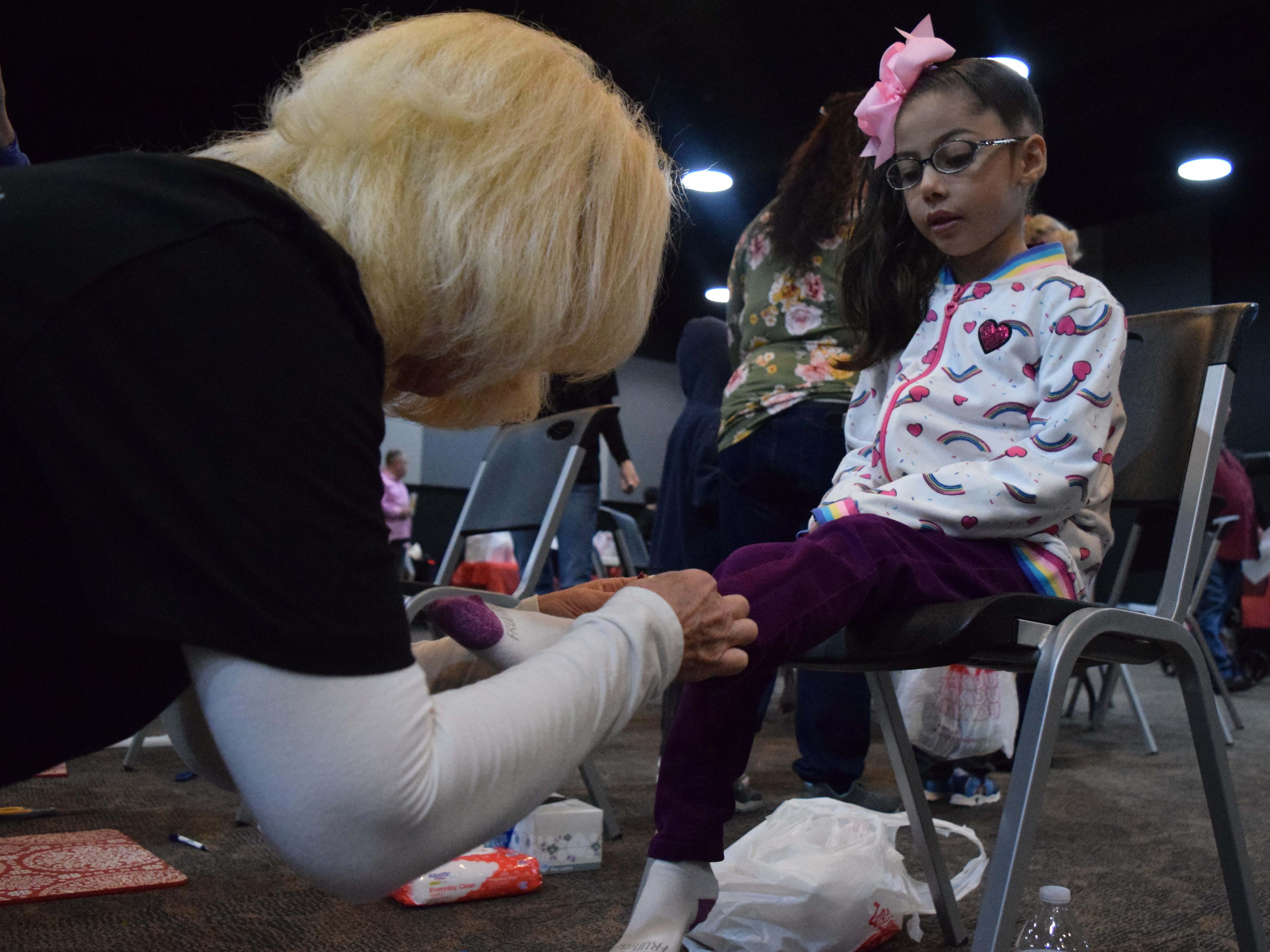 Kelly Shaffner helps put new shoes on Azariah Misquez, 6, at the Soles4Souls event on Saturday, March 9, 2019 at a Las Cruces church.