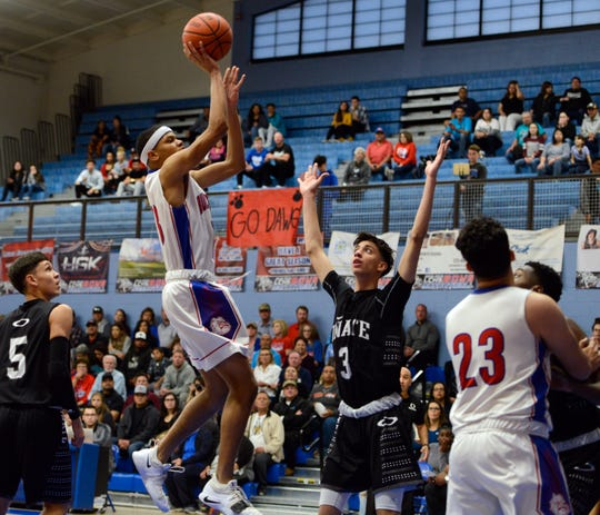Las Cruces High School forward Ray Brown shoots over Oñate s Jordy Moreno during the first quarter of Saturday's state tournament game at Las Cruces High.