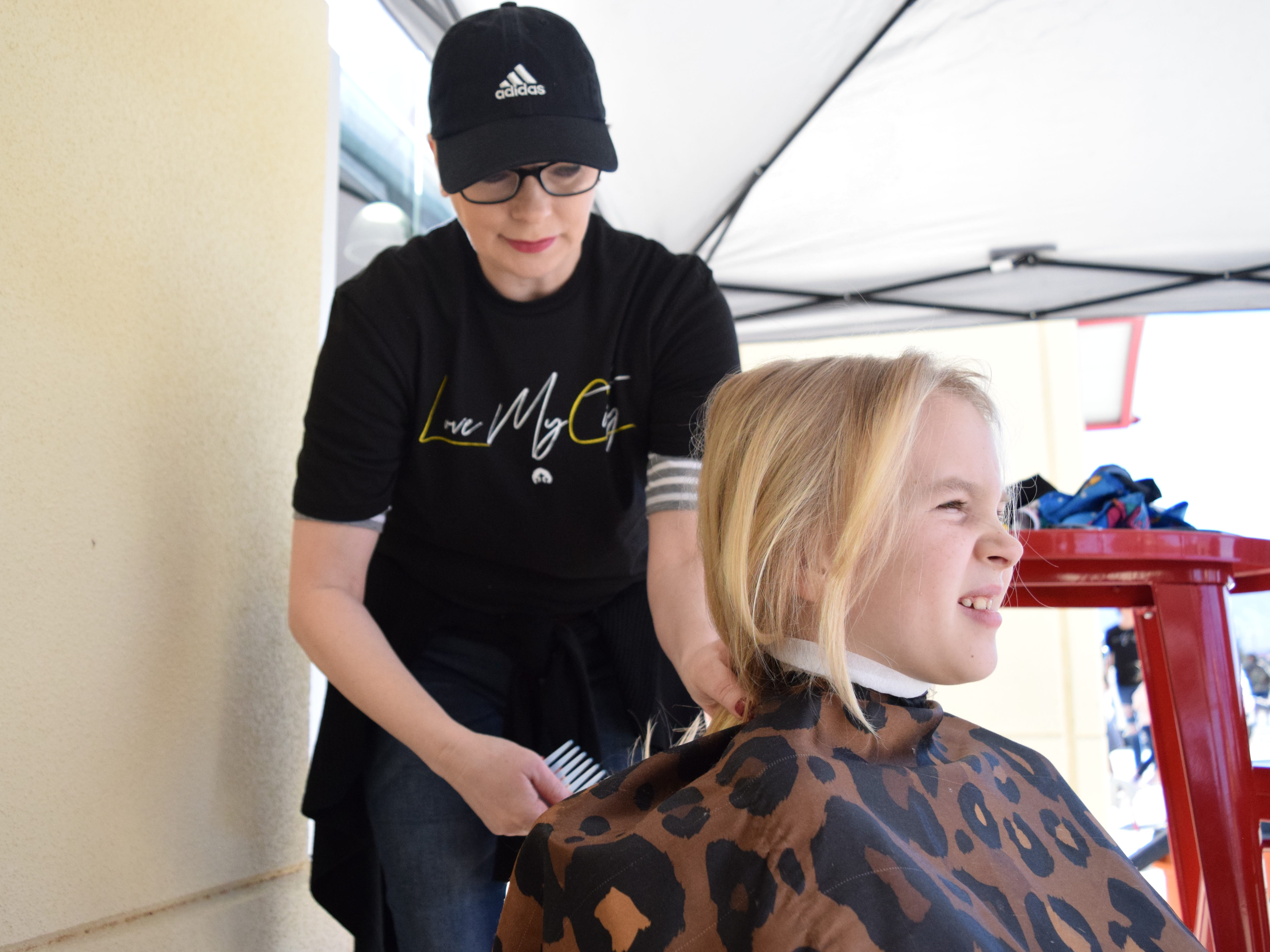 Phoenix Clabaugh, 9, gets a haircut from church member Annette Edmonds as part of Las Cruces First Assembly of God's shoe give-away event on Saturday, March 9, 2019.
