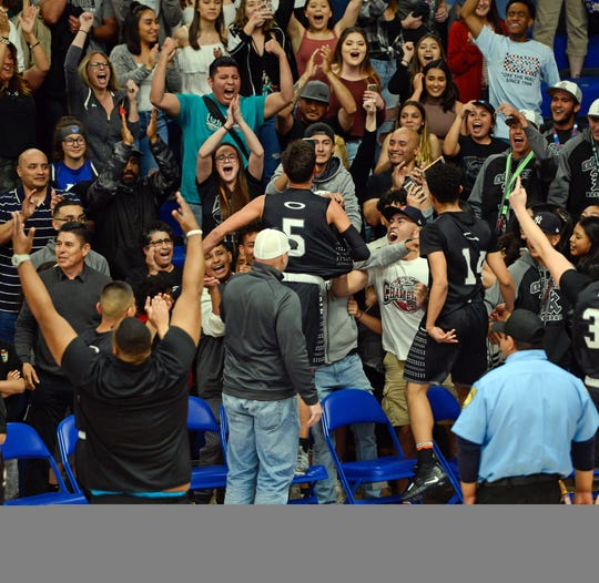 Onate's Ricky Lujan goes into the stand to celebrate the Knights upset win over previously undefeated Las Cruces in the first round of the state high school basketball tournament.