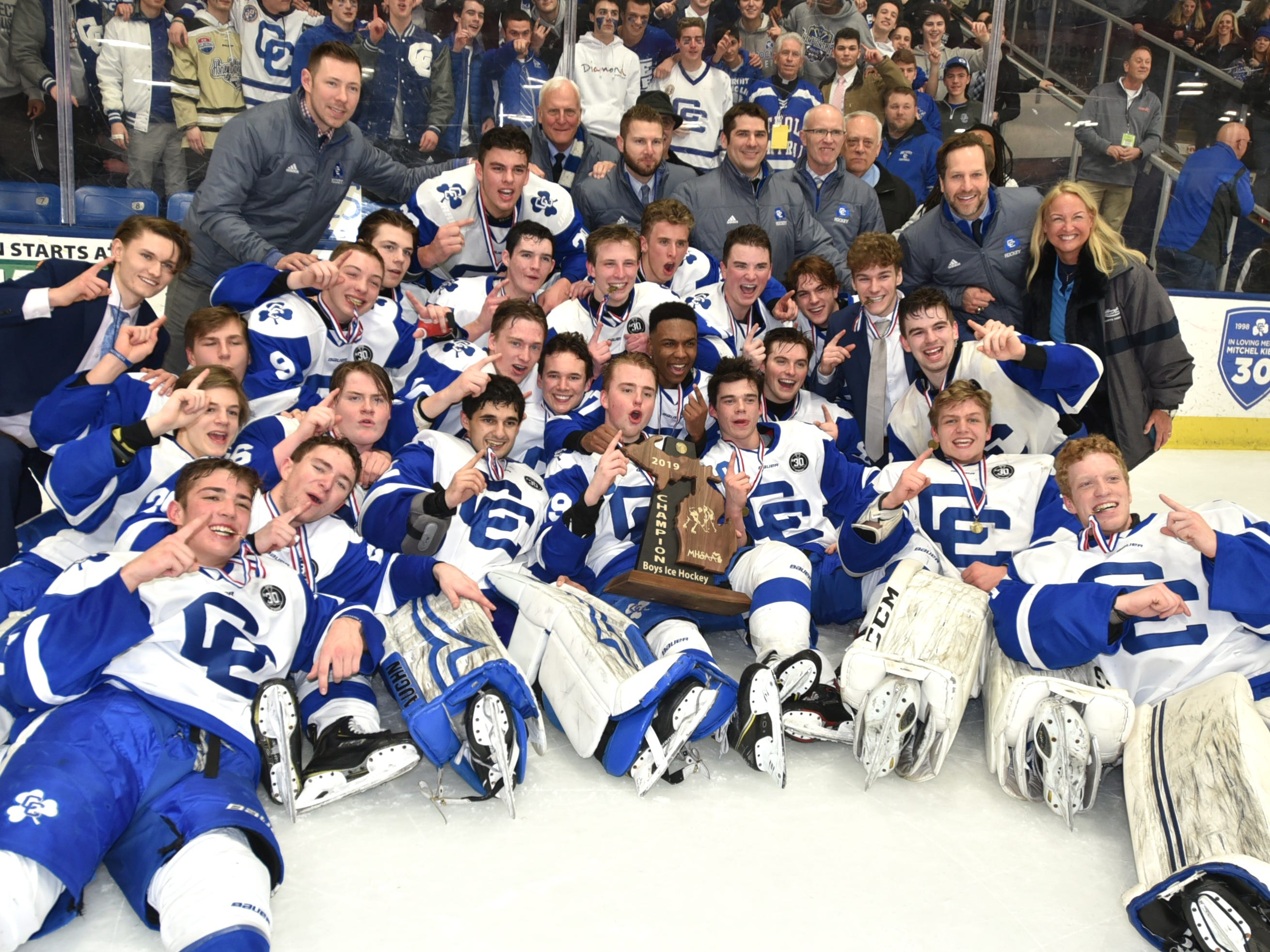 The Detroit Catholic Central Shamrocks pose with their Div. 1 hockey championship trophy on March 9, 2019 at USA Hockey Arena in Plymouth.
