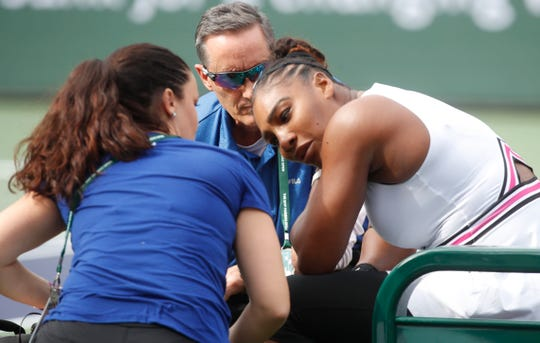 Serena Williams is attended by medical staff  during her match against Garbiñe Muguruza on Stadium One at the 2019 BNP Paribas Open at Indian Wells Tennis Garden on March 10, 2019.