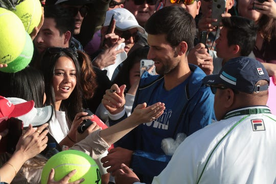 Novak Djokovic signs a fan's arm after practicing at the BNP Paribas Open, Indian Wells, Calif., March 9, 2019.