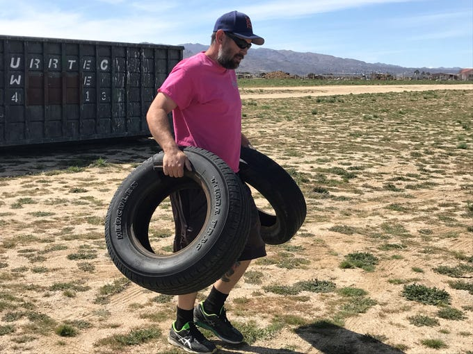 Joshua Tree resident Colin Sauter hauls discarded tires to his trailer on March 9, 2019.