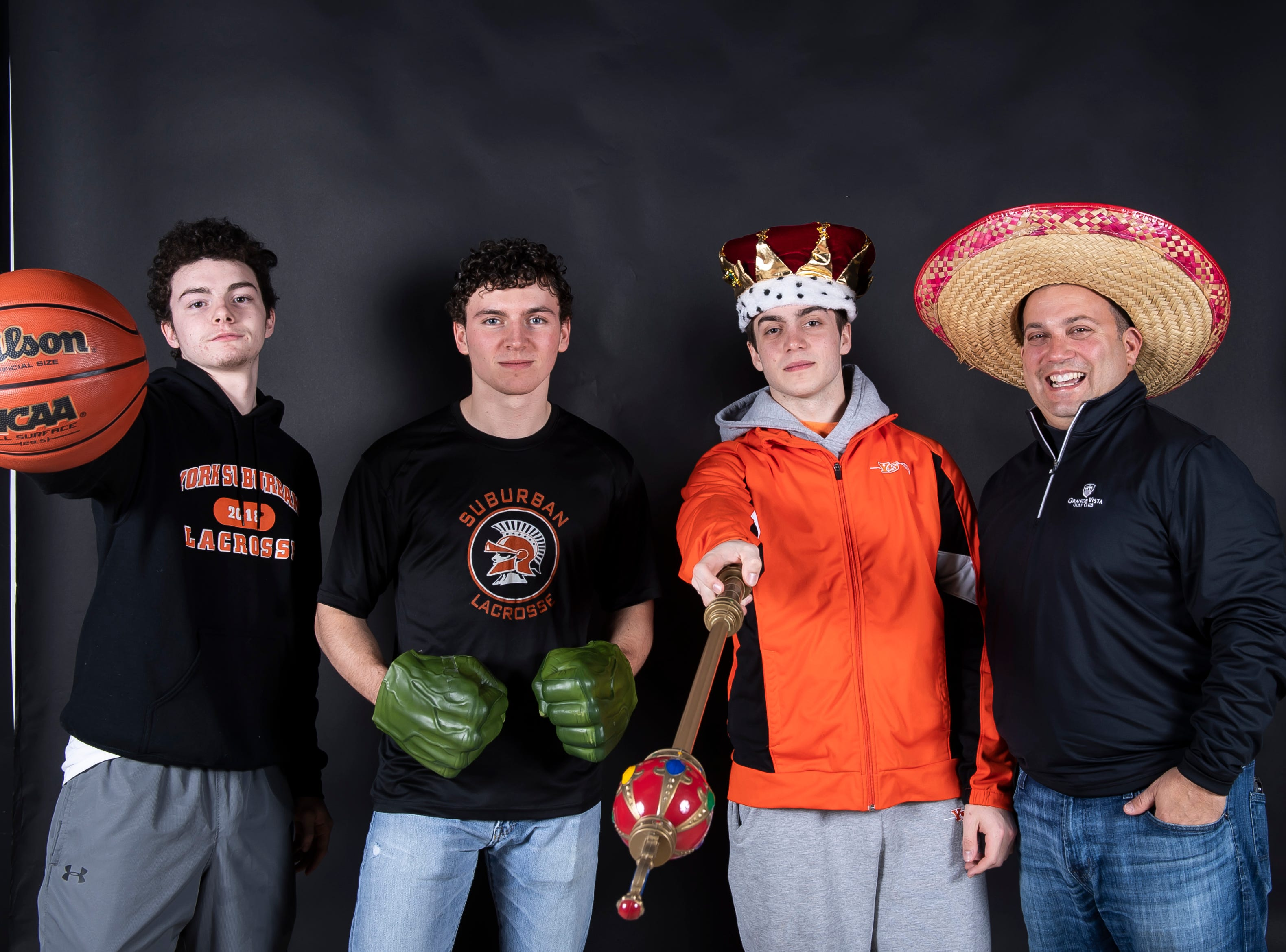 (From left) York Suburban lacrosse's Justin Shocker, Evan Lecates, Dominic Corto and coach Frank Corto strike a pose in the GameTimePA photo booth during spring sports media day in York Sunday, March 10, 2019.