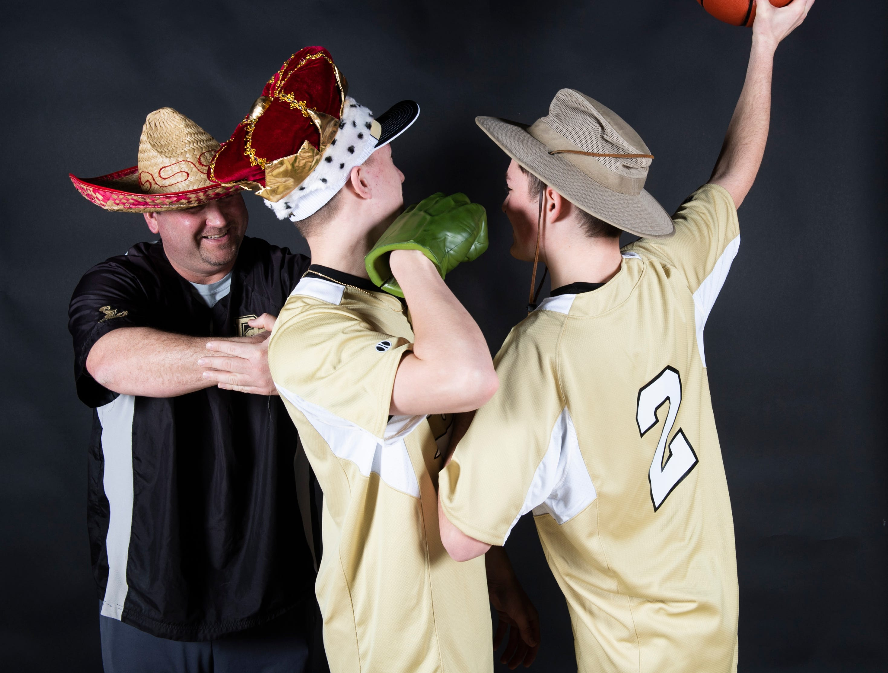 Delone Catholic baseball's Josh Sherdel, right, dunks on teammate Shane Kecken as  coach Dave Neumayer serves as the hoop in the GameTimePA photo booth during spring sports media day in York Sunday, March 10, 2019.