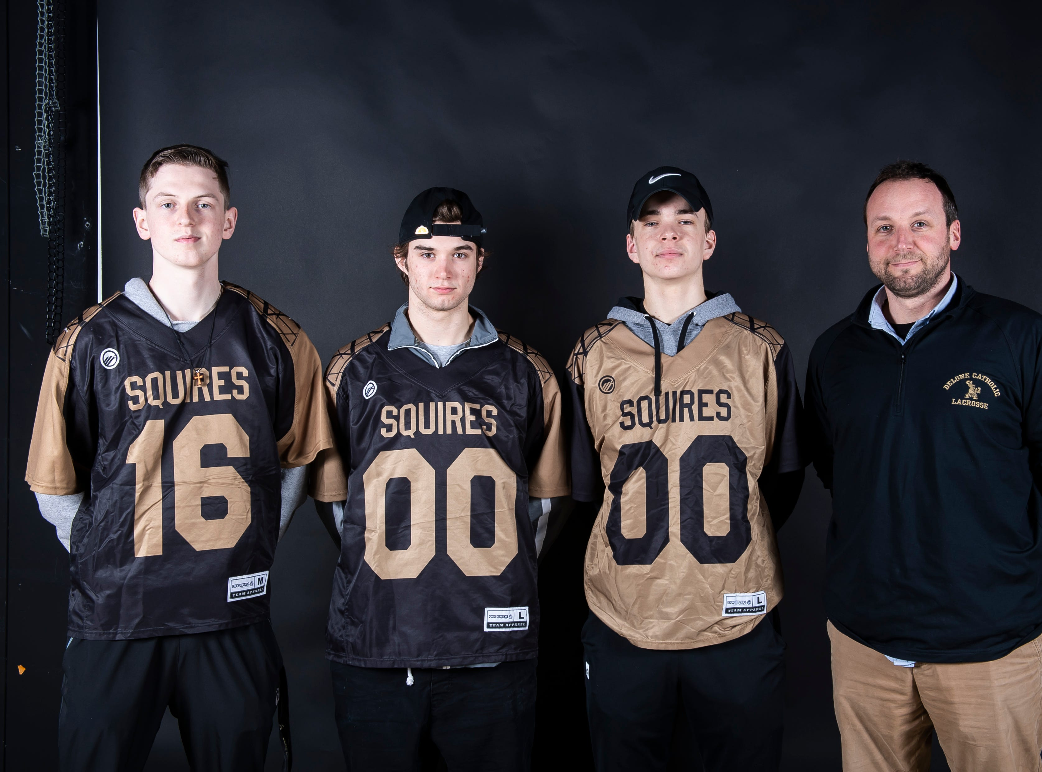 (From left) Delone Catholic lacrosse players Gabe Hall, Dillon Kadis and Luke Panzer pose with coach Wade Smith in the GameTimePA photo booth during spring sports media day in York Sunday, March 10, 2019.