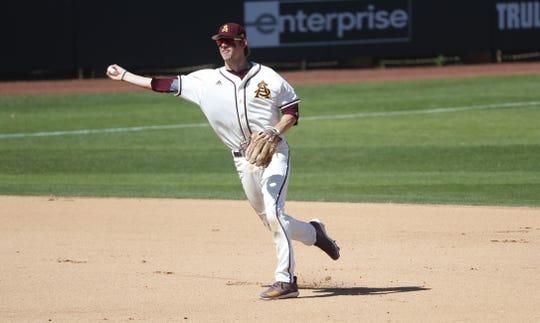 ASU's Gage Workman (14) throws out an Xavier runner at first base at Phoenix Municipal Stadium in Phoenix, Ariz. on March 10, 2019.