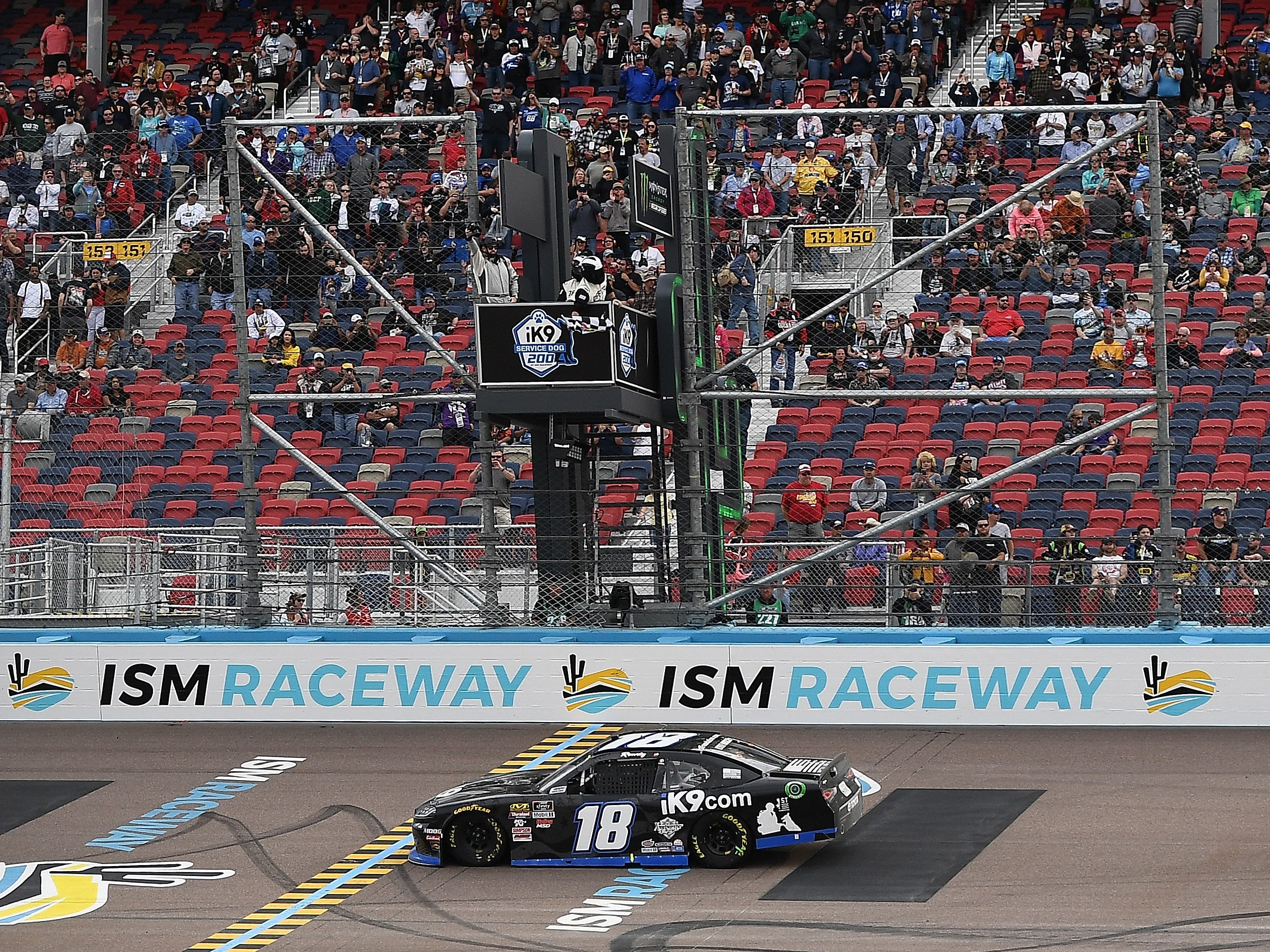 AVONDALE, AZ - MARCH 09:  Kyle Busch, driver of the #18 Extreme Concepts/iK9 Toyota, takes the checkered flag to win the NASCAR Xfinity Series iK9 Service Dog 200 at ISM Raceway on March 9, 2019 in Avondale, Arizona.