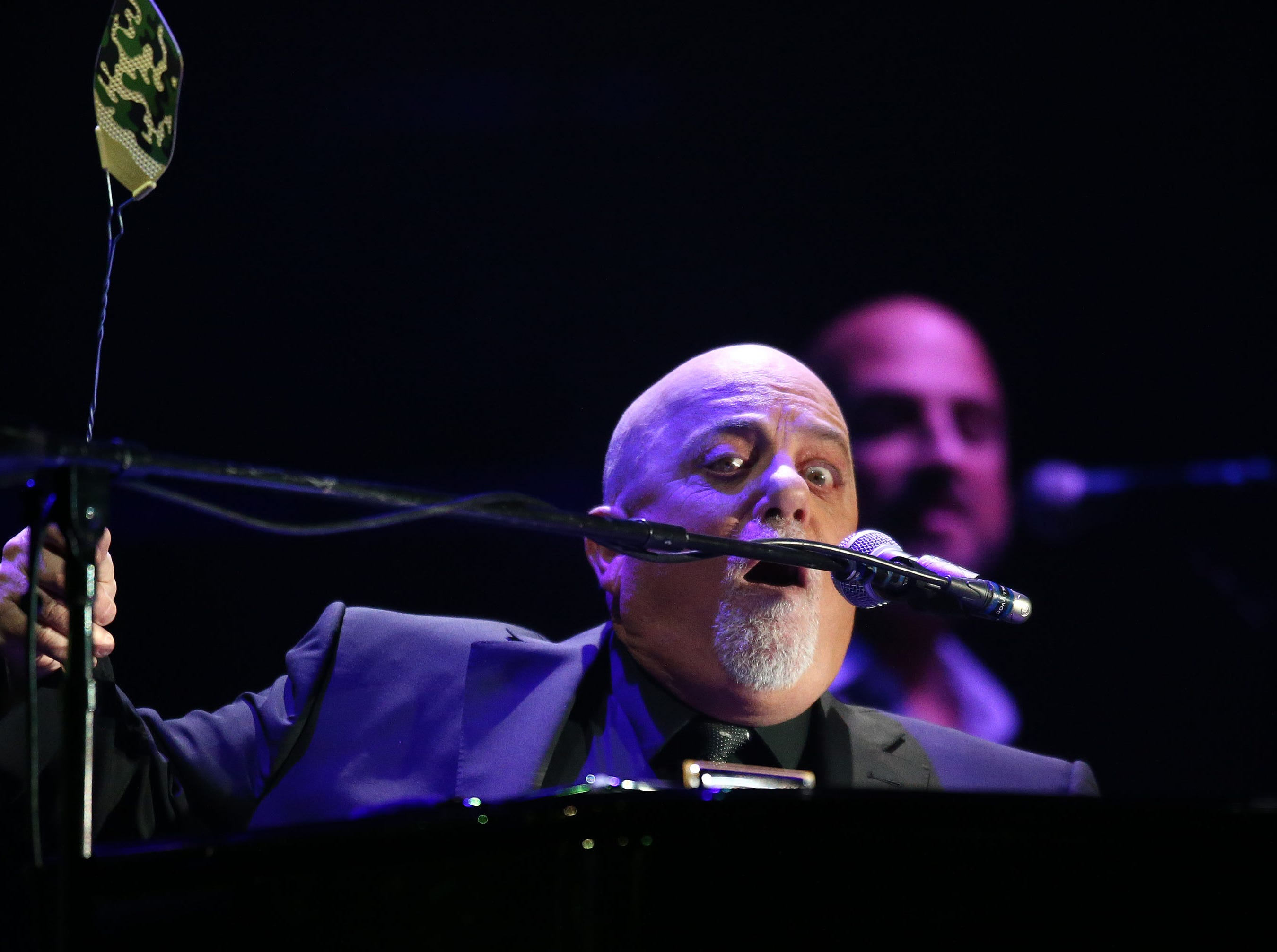 Musician Billy Joel performs while swatting little white moths at Chase Field on March 9, 2019, in Phoenix.