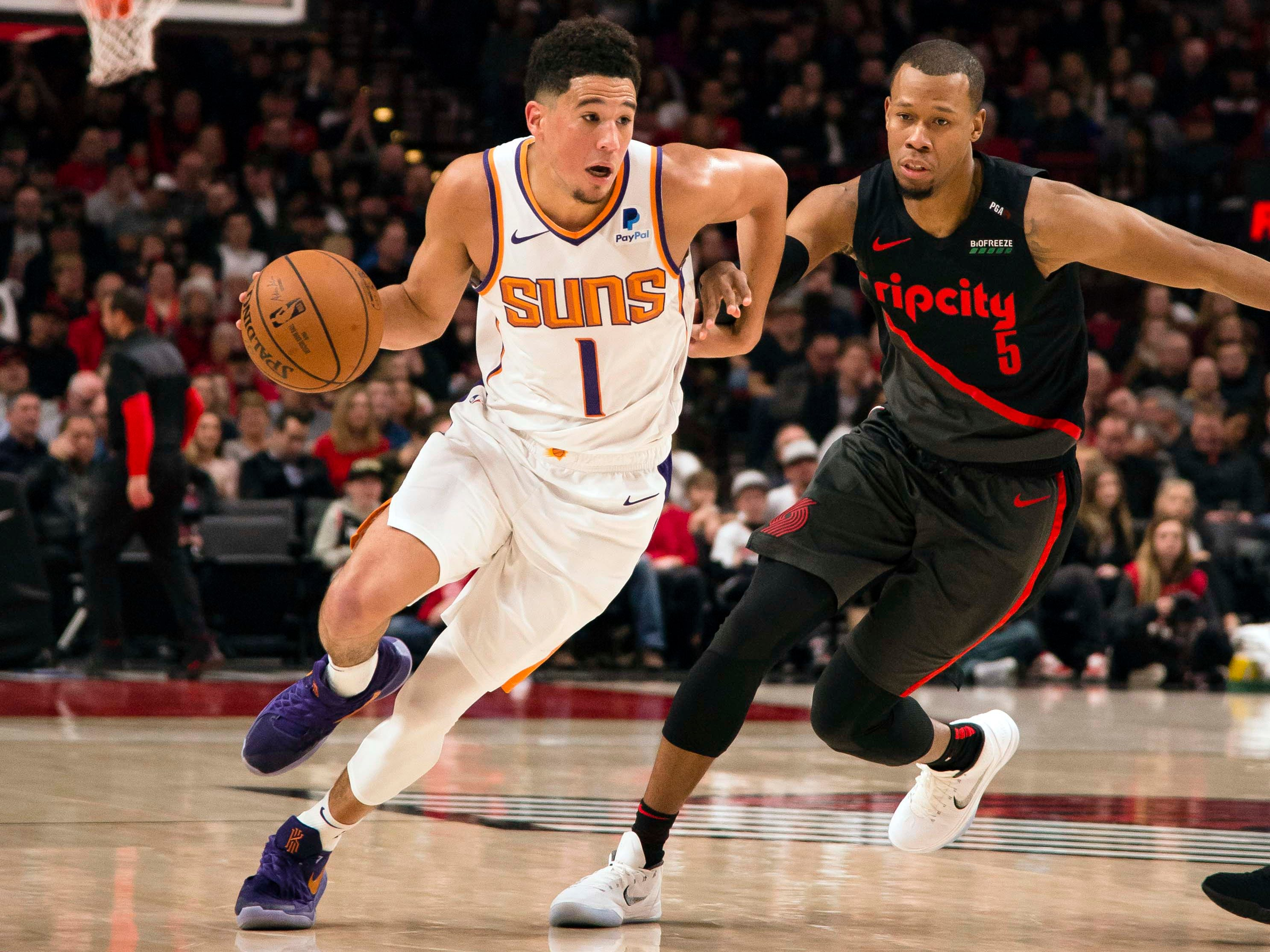 Mar 9, 2019; Portland, OR, USA; Phoenix Suns guard Devin Booker (1) drives past Portland Trail Blazers guard Rodney Hood (5) during the first half at Moda Center.