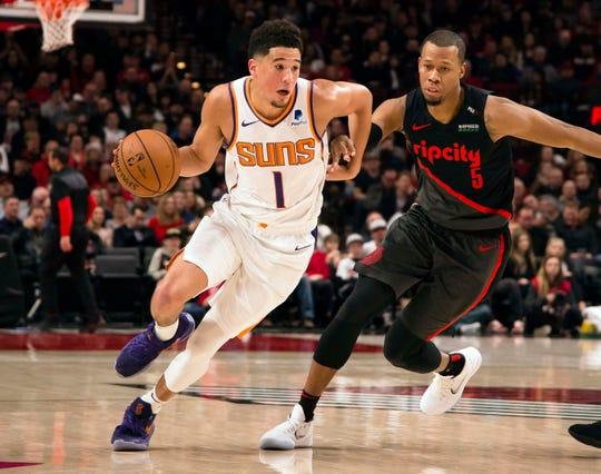 Mar 9, 2019; Portland, OR, USA; Phoenix Suns guard Devin Booker (1) drives past Portland Trail Blazers guard Rodney Hood (5) during the first half at Moda Center.
