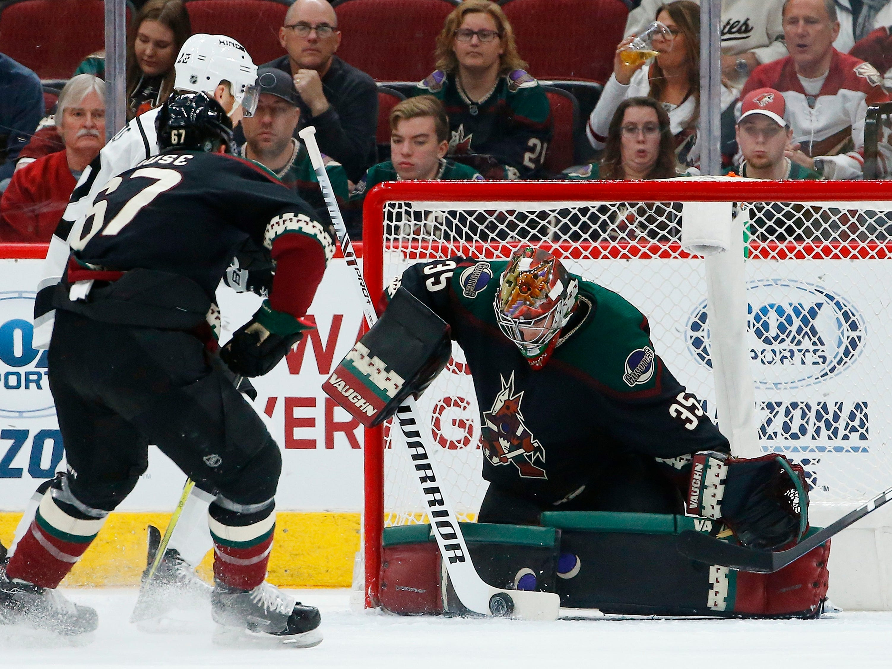 Arizona Coyotes goaltender Darcy Kuemper (35) makes a save on a shot by Los Angeles Kings center Trevor Lewis, back left, as Coyotes left wing Lawson Crouse (67) defends during the second period of an NHL hockey game Saturday, March 9, 2019, in Glendale, Ariz.
