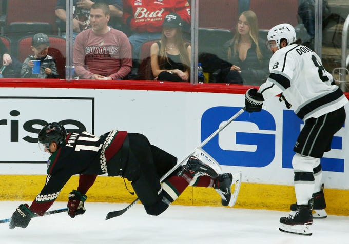 Los Angeles Kings defenseman Drew Doughty (8) trips Arizona Coyotes right wing Richard Panik (14) during the third period of an NHL hockey game Saturday, March 9, 2019, in Glendale, Ariz. The Coyotes defeated the Kings 4-2.