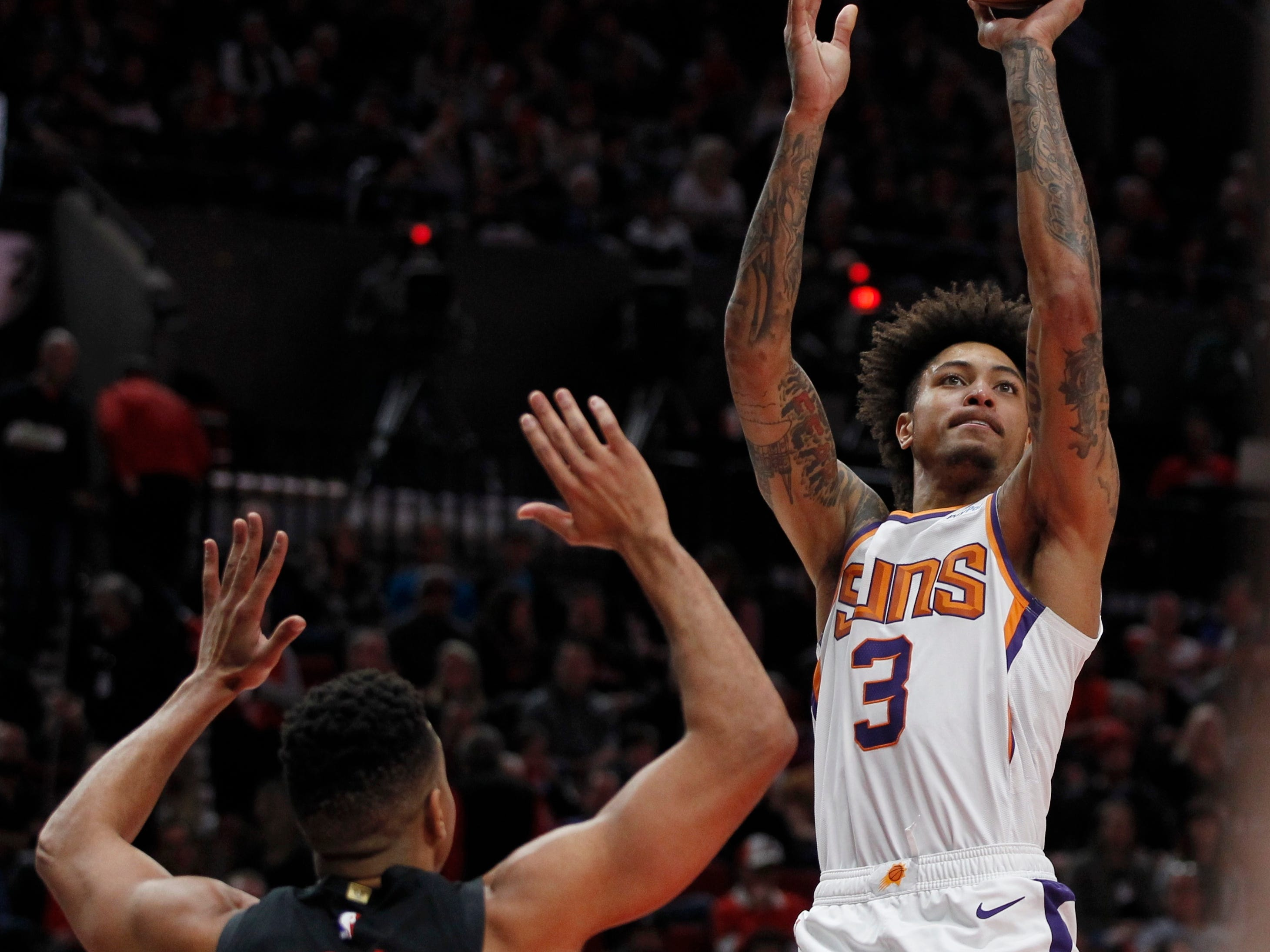 Phoenix Suns forward Kelly Oubre Jr., right, shoots as Portland Trail Blazers guard CJ McCollum defends during the first half of an NBA basketball game in Portland, Ore., Saturday, March 9, 2019.
