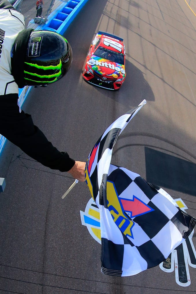 AVONDALE, AZ - MARCH 10:  Kyle Busch, driver of the #18 Skittles Toyota, takes the checkered flag to win the Monster Energy NASCAR Cup Series TicketGuardian 500 at ISM Raceway on March 10, 2019 in Avondale, Arizona.  (Photo by Daniel Shirey/Getty Images)