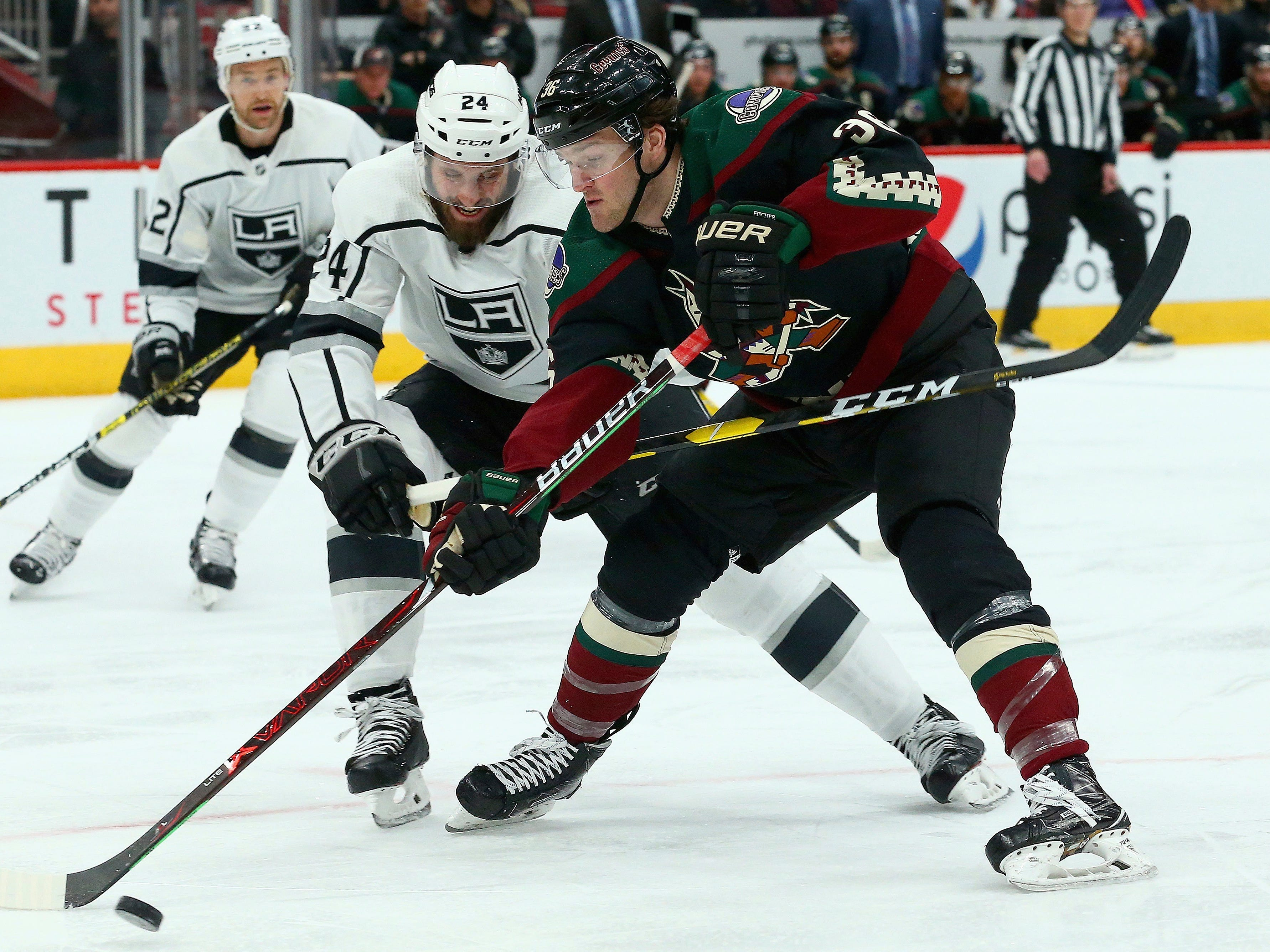 Arizona Coyotes right wing Christian Fischer (36) tries to get off a shot as Los Angeles Kings defenseman Derek Forbort (24) applies pressure while Kings center Trevor Lewis, left, looks on during the second period of an NHL hockey game Saturday, March 9, 2019, in Glendale, Ariz.