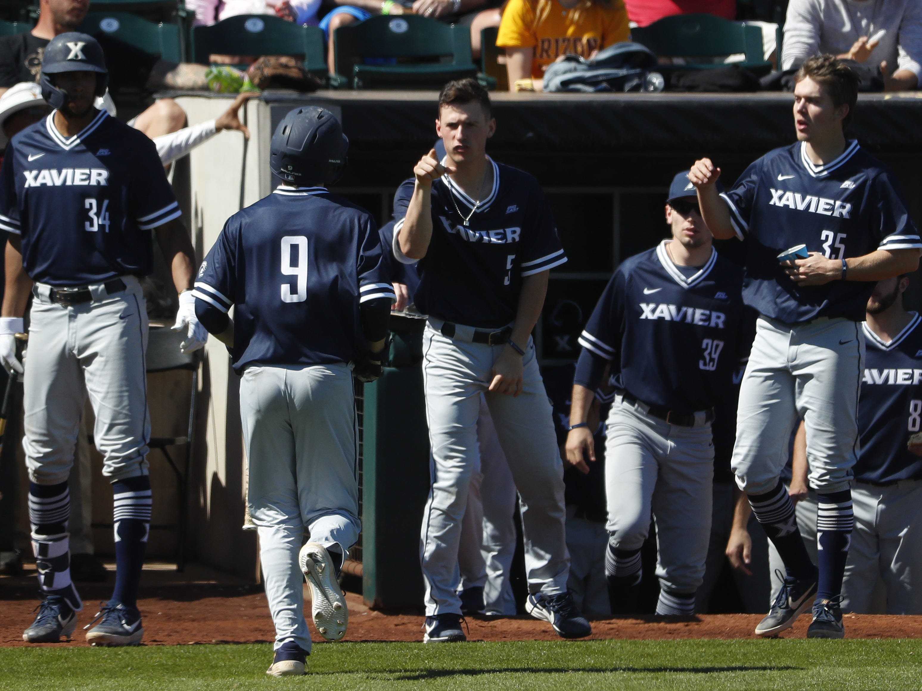 Xavier's Ryan Altenberger (9) celebrates with his teammates after scoring during a game against ASU at Phoenix Municipal Stadium in Phoenix, Ariz. on March 10, 2019.