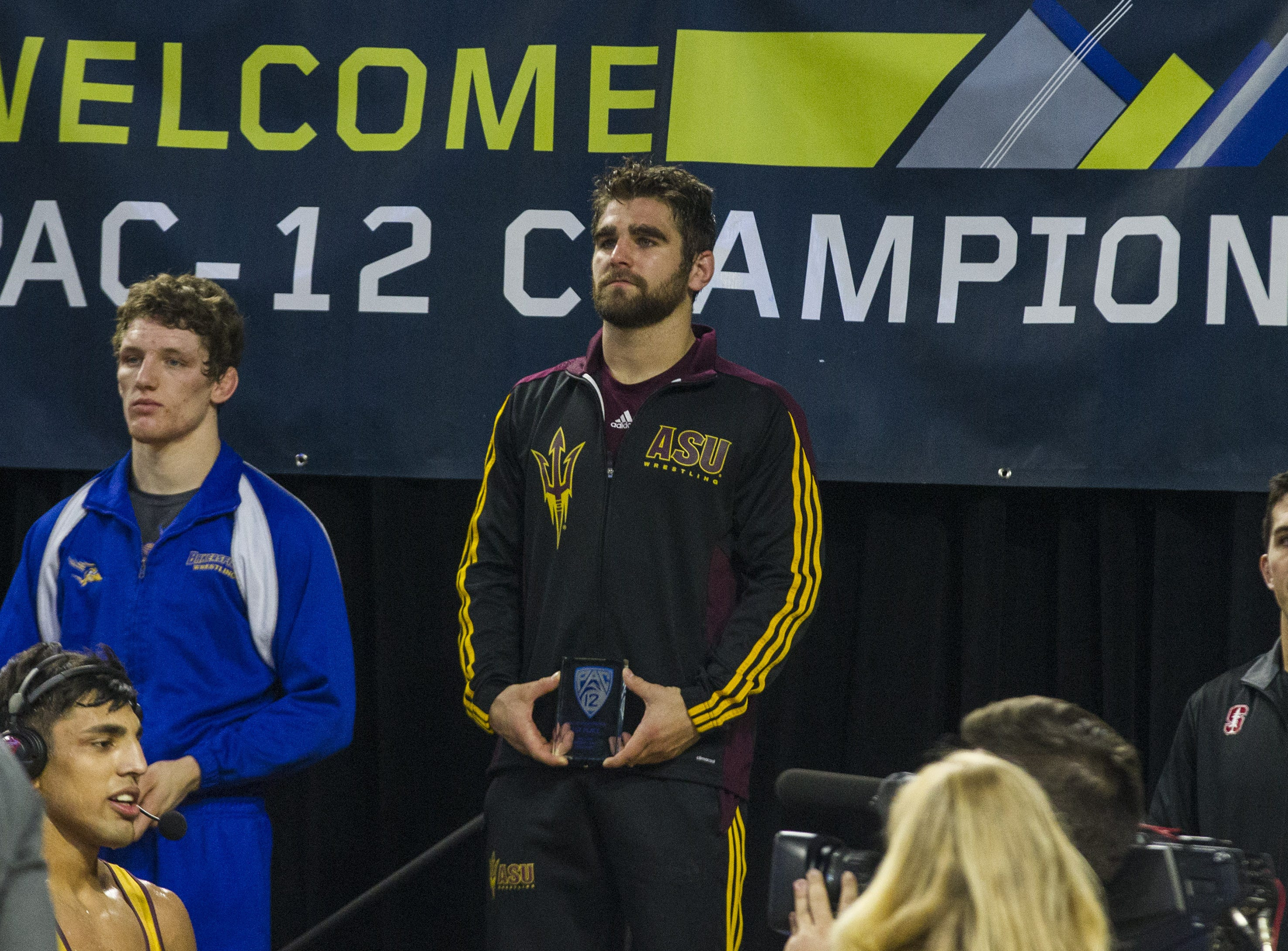 ASU's Josh Shields receives his trophy for his win over CSU Bakersfield's Jacob Thalin in the 165 pound weight class during the Pac 12 Wrestling Championship at Wells Fargo Arena in Tempe on March 9, 2019.