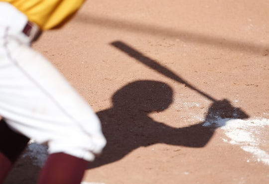 A shadow of a Mountain Pointe batter during a high school softball game at Mountain Pointe on March 23, 2018.