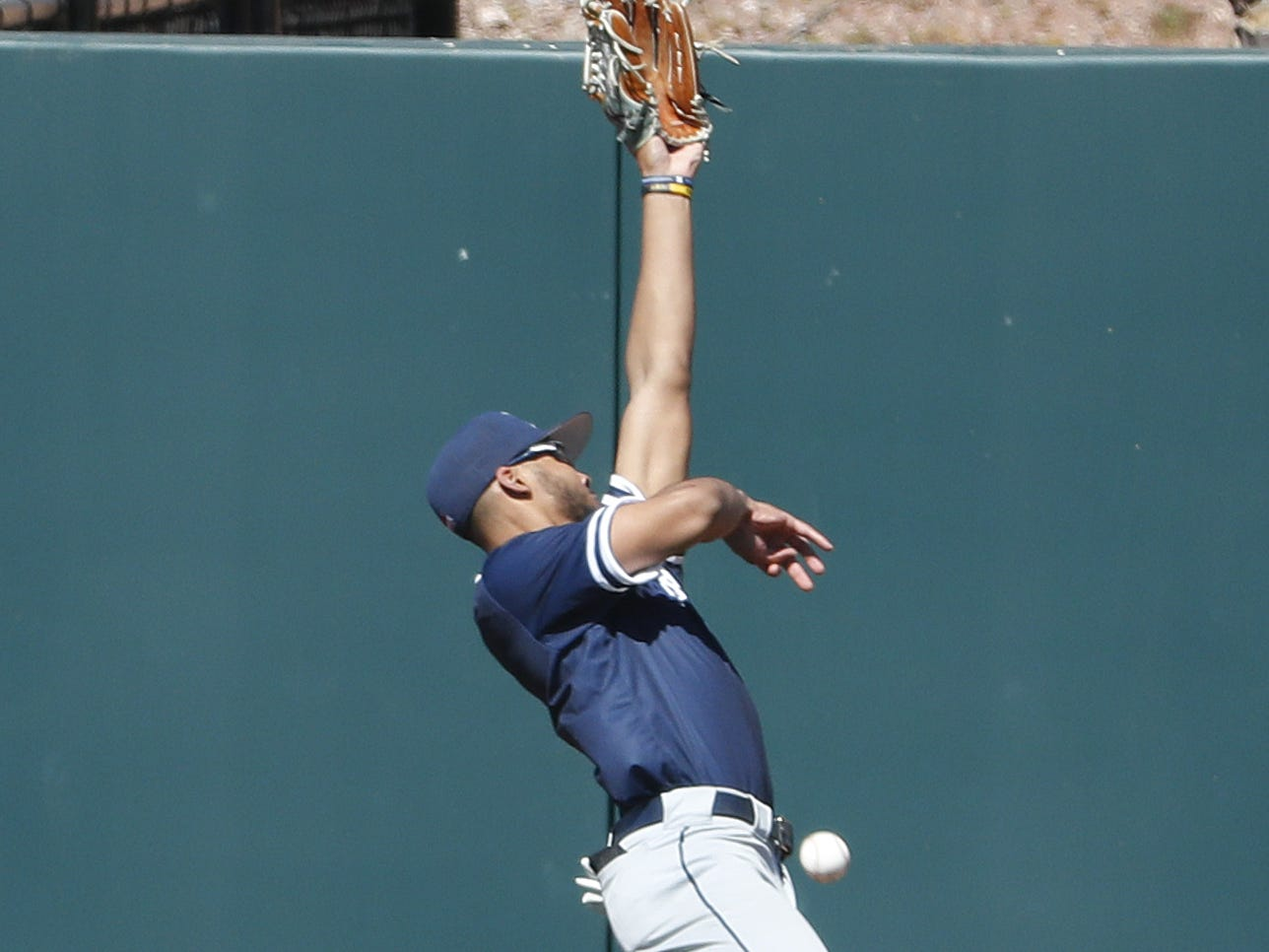 Xavier's Allbry Major (34) can't come down with a leaping catch near the wall during a game against ASU at Phoenix Municipal Stadium in Phoenix, Ariz. on March 10, 2019.