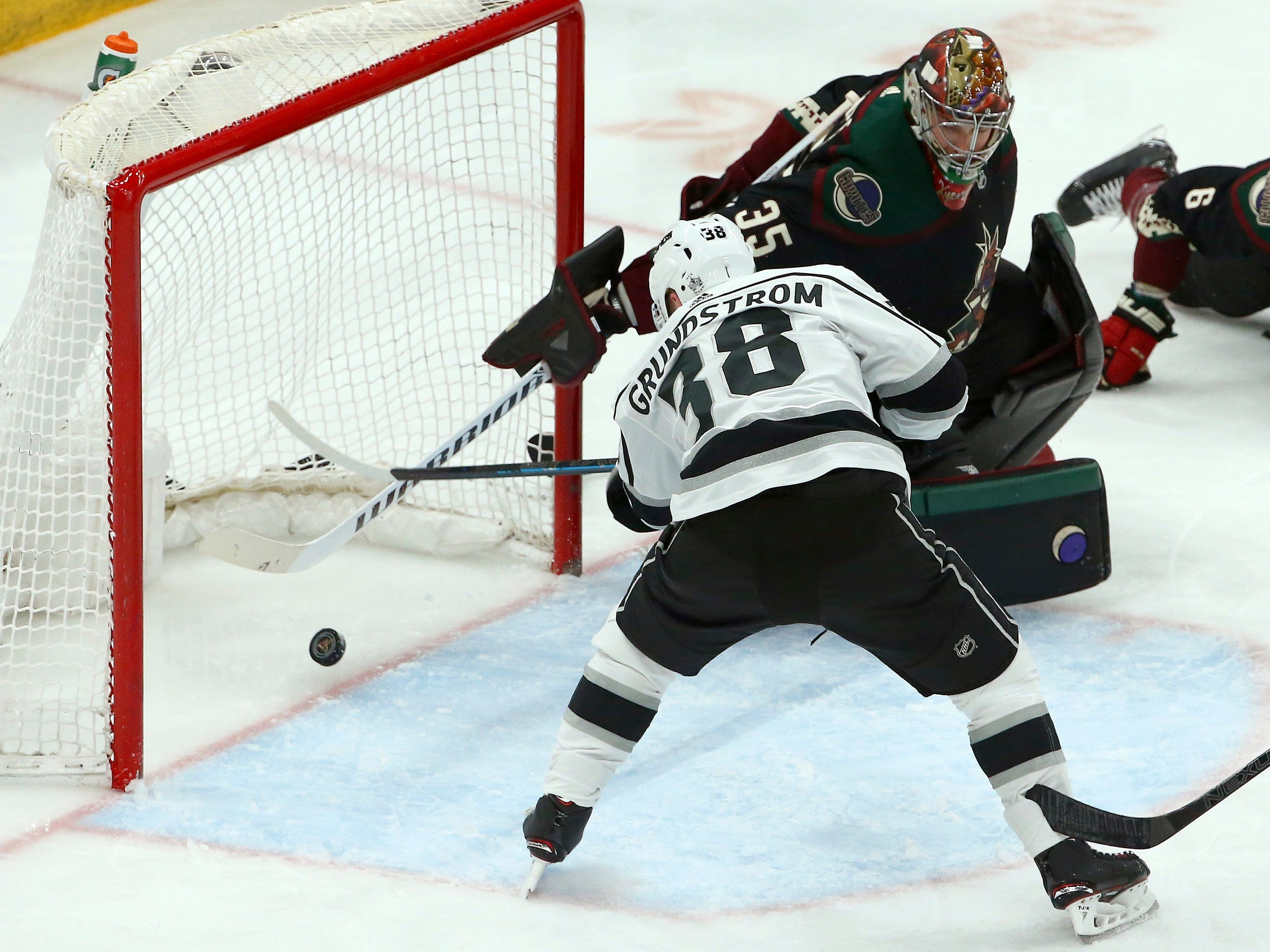 Los Angeles Kings right wing Carl Grundstrom (38) scores a goal against Arizona Coyotes goaltender Darcy Kuemper, top right, during the third period of an NHL hockey game Saturday, March 9, 2019, in Glendale, Ariz. For the Kings' Grundstrom it was his first NHL goal in his first game, but the Coyotes defeated the Kings 4-2.