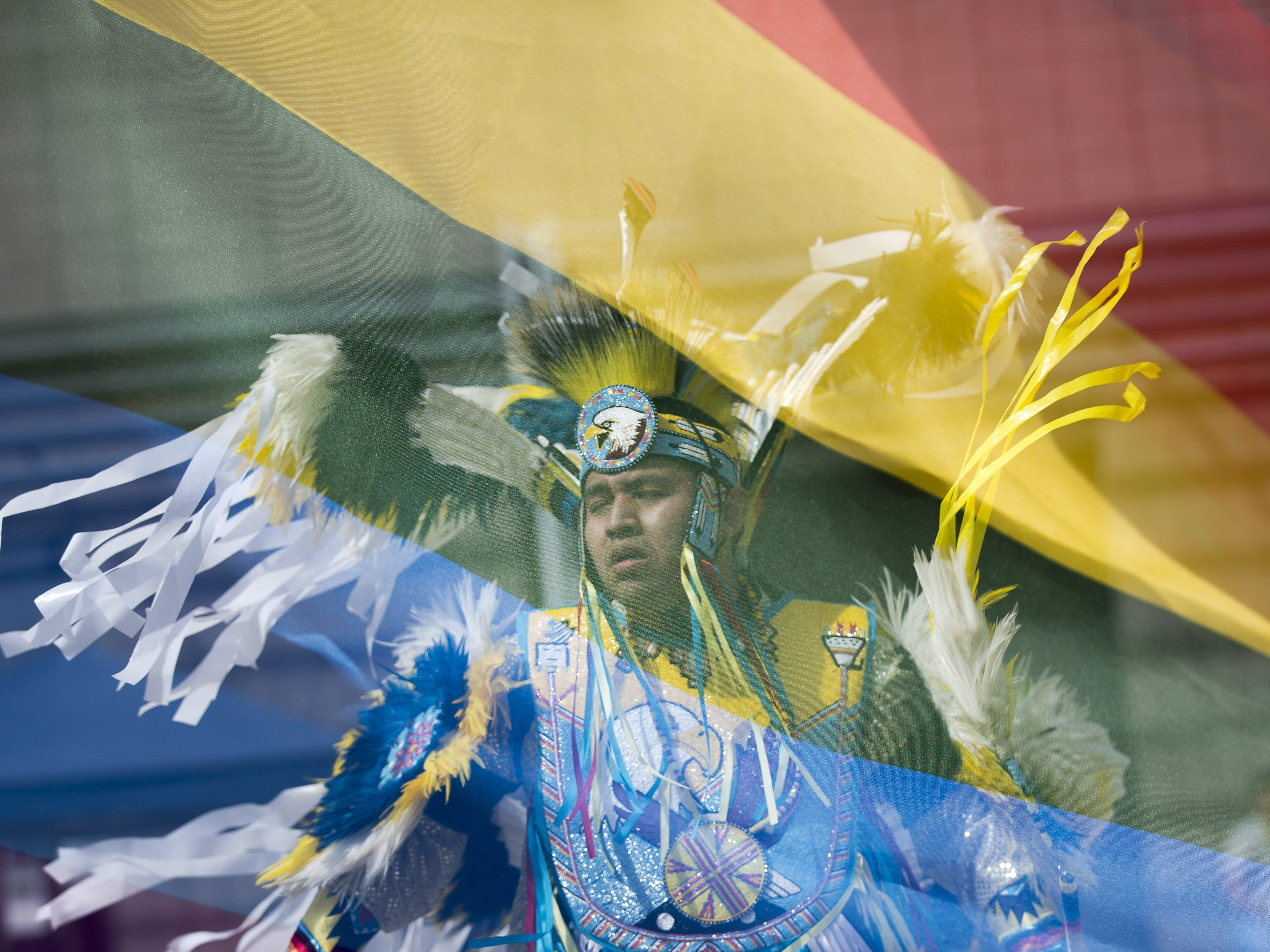 In this double exposure, Cody Thompson performs a feather dance at the Native Two Spirit Powwow and a pride flag blows in the wind at South Mountain Community College in Phoenix, Ariz. on Saturday, March 9, 2019. The powwow was the first of its kind in Arizona, featuring members who identified as two spirit, and members who did not, dancing together.