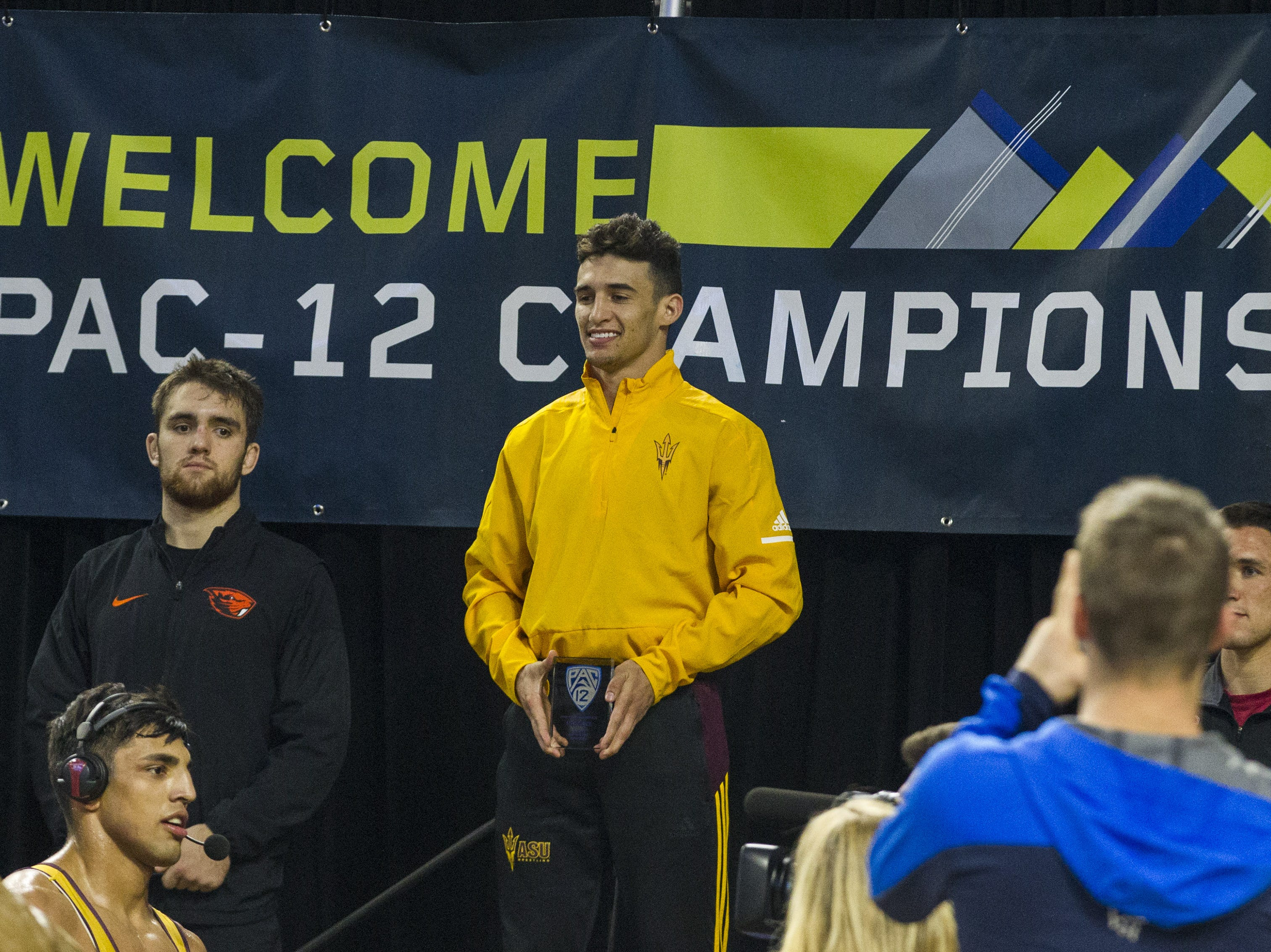ASU's Christian Pagdilao receives his trophy for his win over Oregon State's Hunter Willits in the 157 pound weight class during the Pac 12 Wrestling Championship at Wells Fargo Arena in Tempe on March 9, 2019.