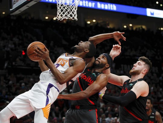 Phoenix Suns forward Josh Jackson, left, prepares to shoot as Portland Trail Blazers forward Maurice Harkless, center, and center Jusuf Nurkic, right, defend during the first half of an NBA basketball game in Portland, Ore., Saturday, March 9, 2019.