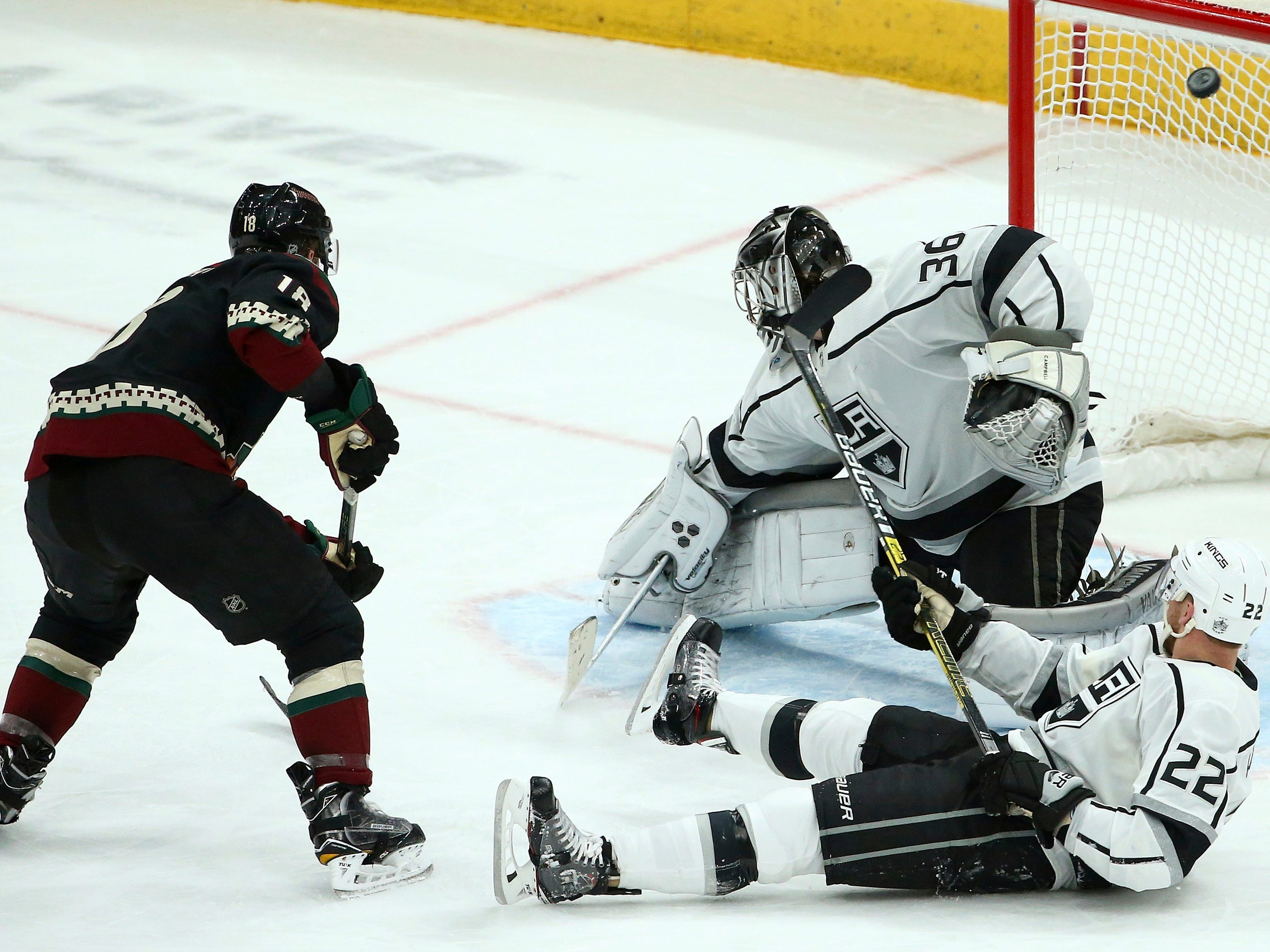 Arizona Coyotes center Christian Dvorak, left, scores a goal against Los Angeles Kings goaltender Jack Campbell (36) as Kings center Trevor Lewis (22) slides along on the ice during the third period of an NHL hockey game Saturday, March 9, 2019, in Glendale, Ariz. The Coyotes defeated the Kings 4-2.
