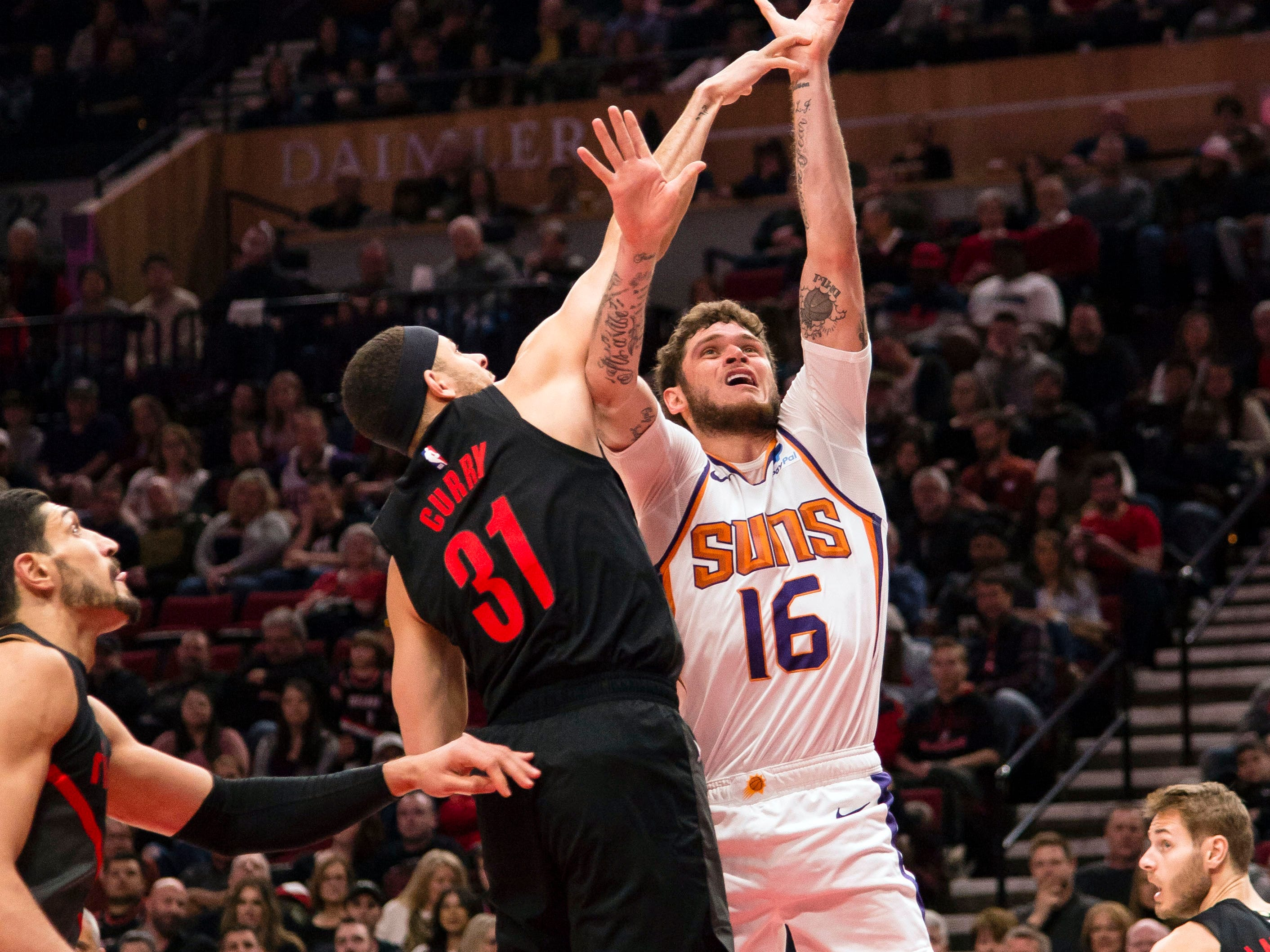 Mar 9, 2019; Portland, OR, USA; Phoenix Suns guard Tyler Johnson (16) shoots a basket against Portland Trail Blazers guard Seth Curry (31) during the first half at Moda Center.