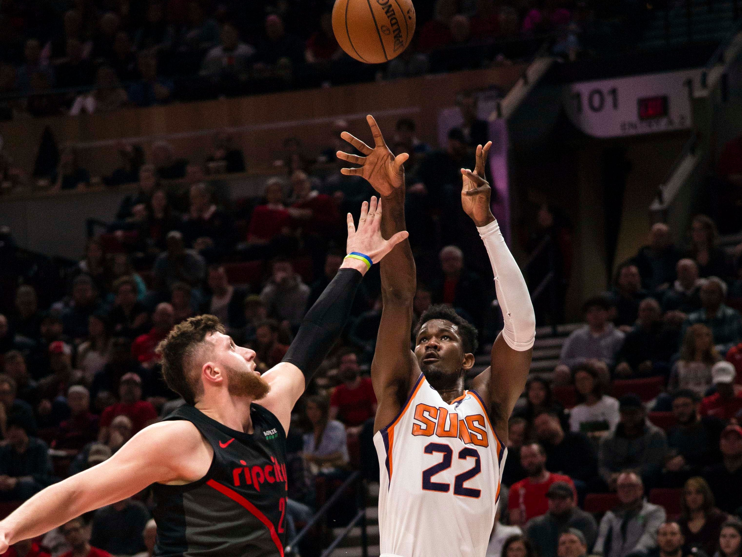 Mar 9, 2019; Portland, OR, USA; Phoenix Suns center Deandre Ayton (22) shoots a basket against Portland Trail Blazers center Jusuf Nurkic (27) during the first half at Moda Center.