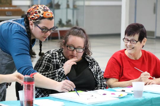 "Local artist Mackenzie Warren, of Oak Tree Art Studio, helps out Lexa Beard and Cathy Broadfield during the ""Side by Side Art"" class in honor of National Developmental Disabilities Awareness Month."