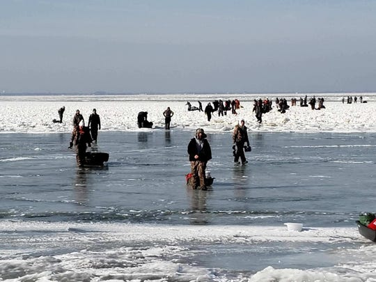 Ice fishermen walk to land after being stuck on an ice floe that broke free from land north of Catawaba Island, March 9, 2019. 46 people were rescued by Coast Guard and local agencies via airboats and approximately 100 people were able to self-rescue by walking across ice-bridges or swimming in the water.