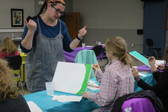 "Local artist Mackenzie Warren, of Oak Tree Art Studio, helps out a student during the ""Side by Side Art"" class in honor of National Developmental Disabilities Awareness Month."