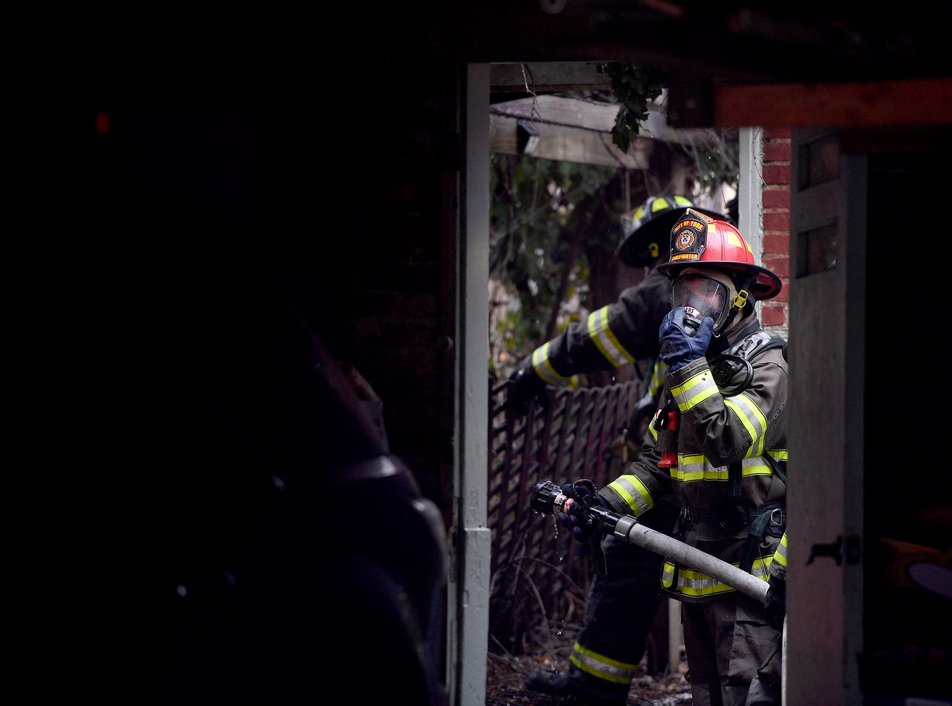 A firefighter adjusts his respirator while battling a stubborn blaze in a two-story garage in the 600 block of W. Philadelphia Street, Sunday, March 10, 2018.