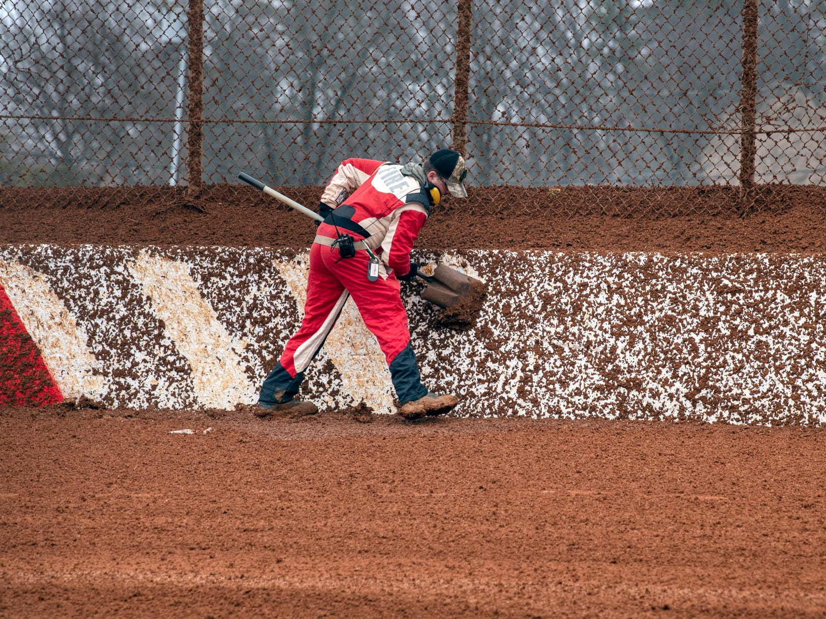 The track crew shovels mud from track wall markers that were obscured by cars shooting mud against the wall during the Lincoln Speedway Ice Breaker 30 on Sunday near Abbottstown.