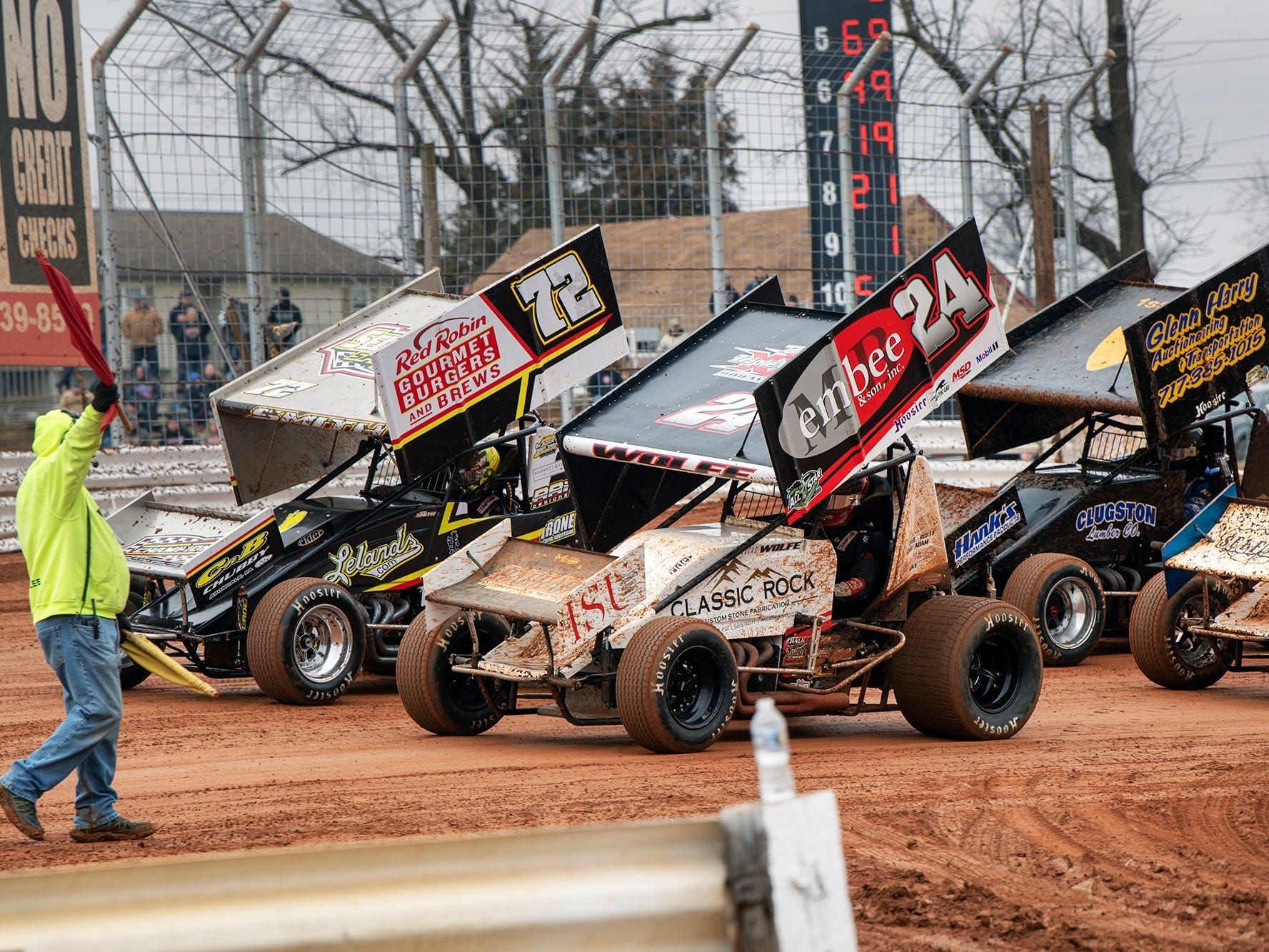 A crewman signals a red flag as cars circle the track during the Lincoln Speedway Ice Breaker 30 on Sunday near Abbottstown.