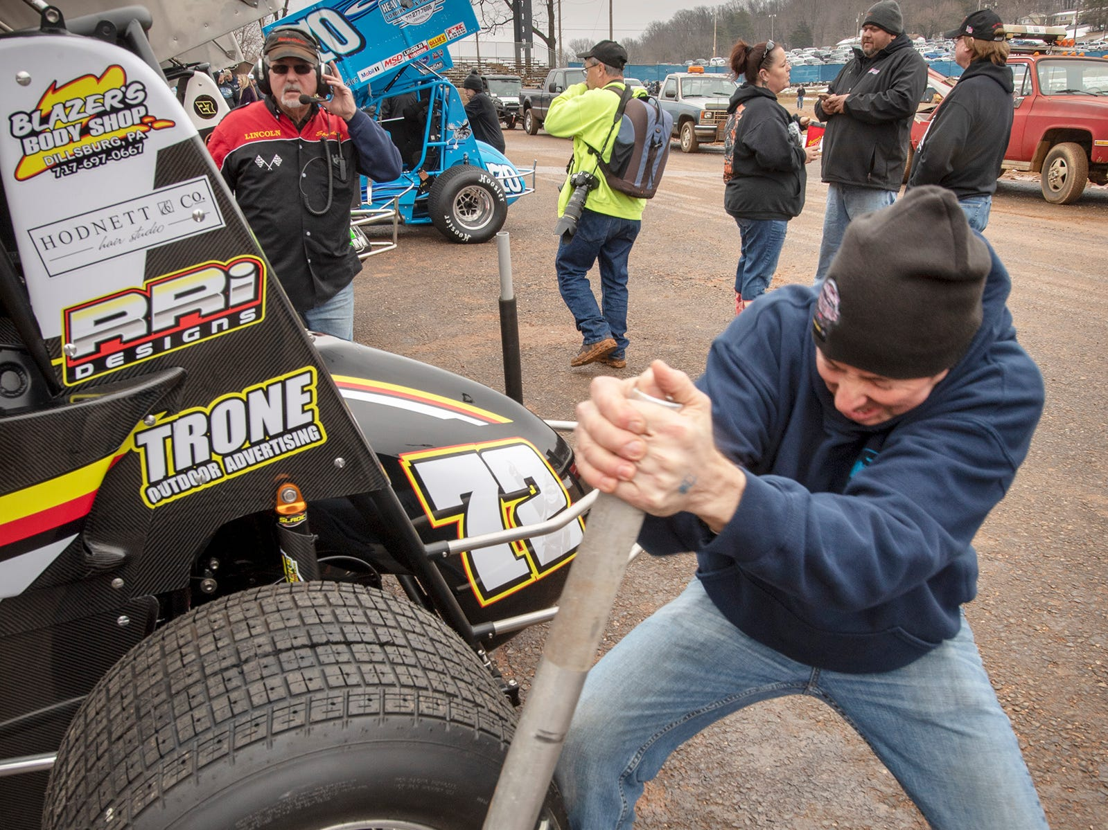 Pit crewman Ron Smith tightens a wheel on the 72 car driven by Ryan Smith during the Lincoln Speedway Ice Breaker 30 on Sunday near Abbottstown.