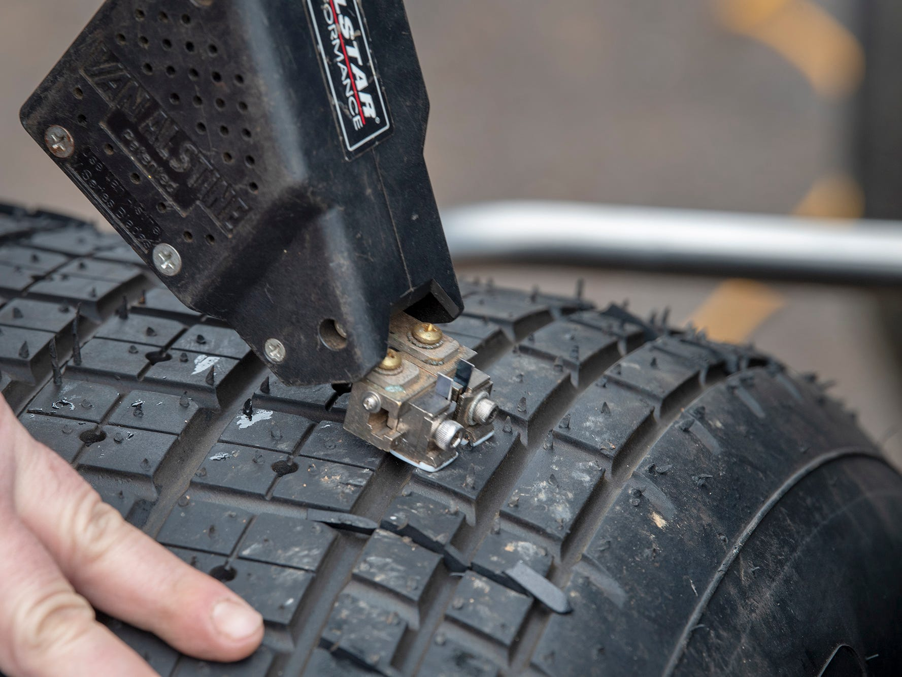 A device is used to add cuts in a tire to help traction on the muddy surface during the Lincoln Speedway Ice Breaker 30 on Sunday near Abbottstown.