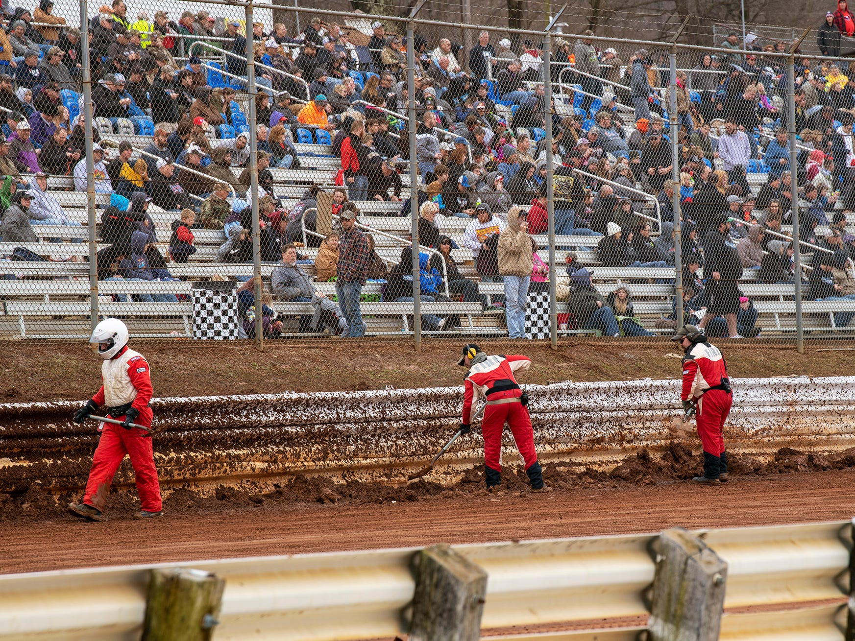 The track crew shovels mud from edge of the track wall that was pushed up by cars running the oval during the Lincoln Speedway Ice Breaker 30 on Sunday near Abbottstown.