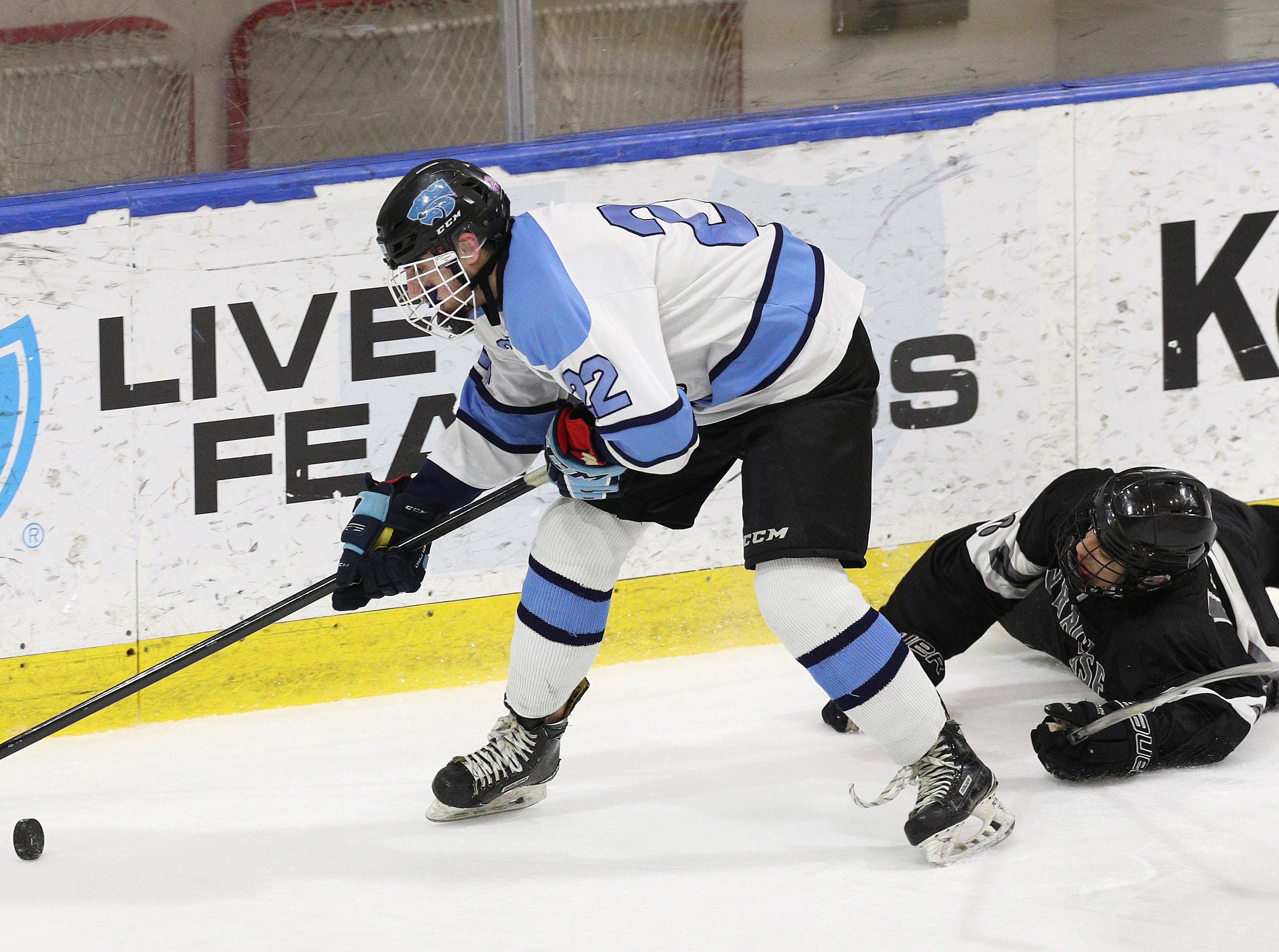 Suffern's Josh Abbott controls the puck behind the net in front of Syracuse's Skariwate Papineau.