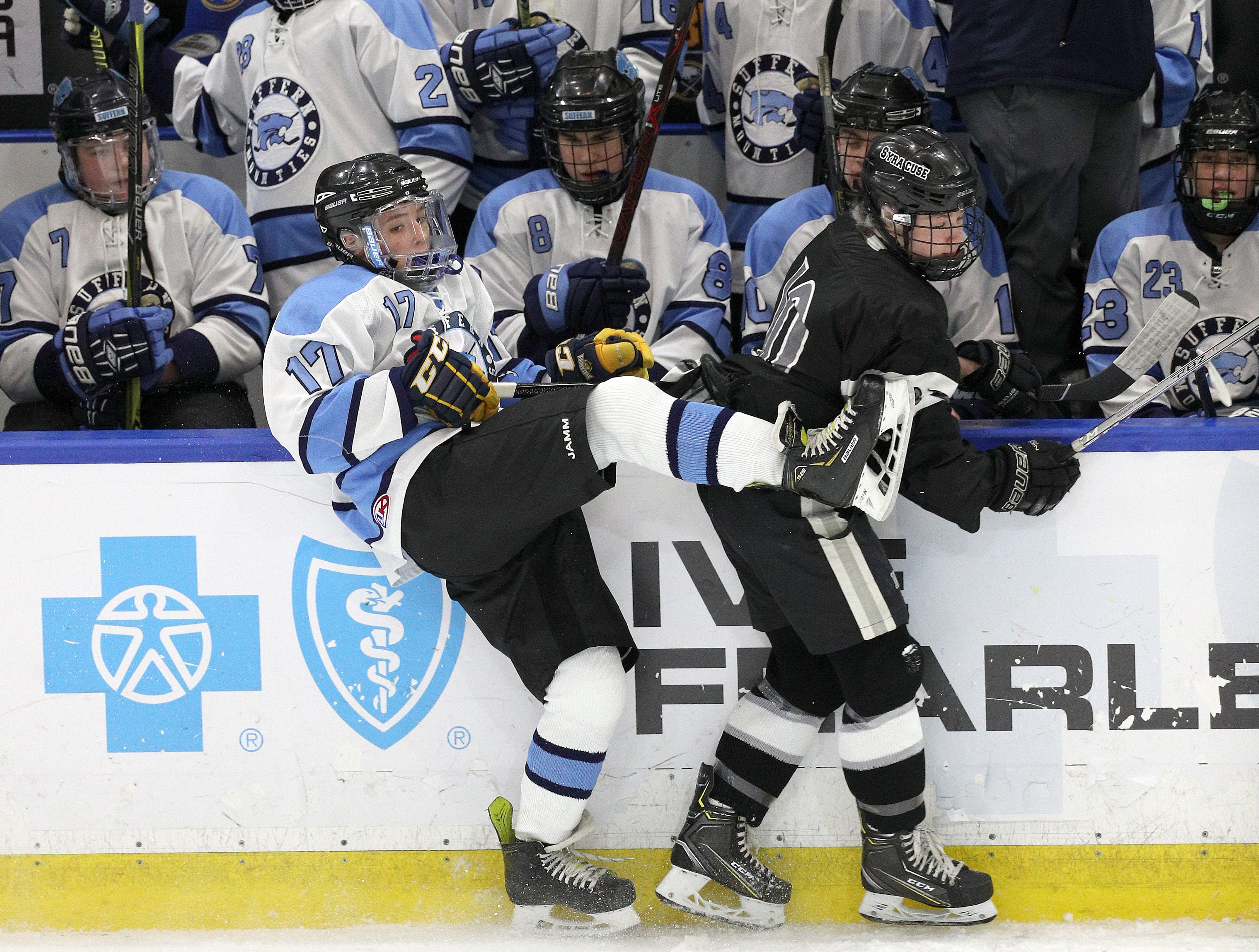 Suffern's Ben Burns is checked along the boards by Syracuse's Skariwate Papineau.